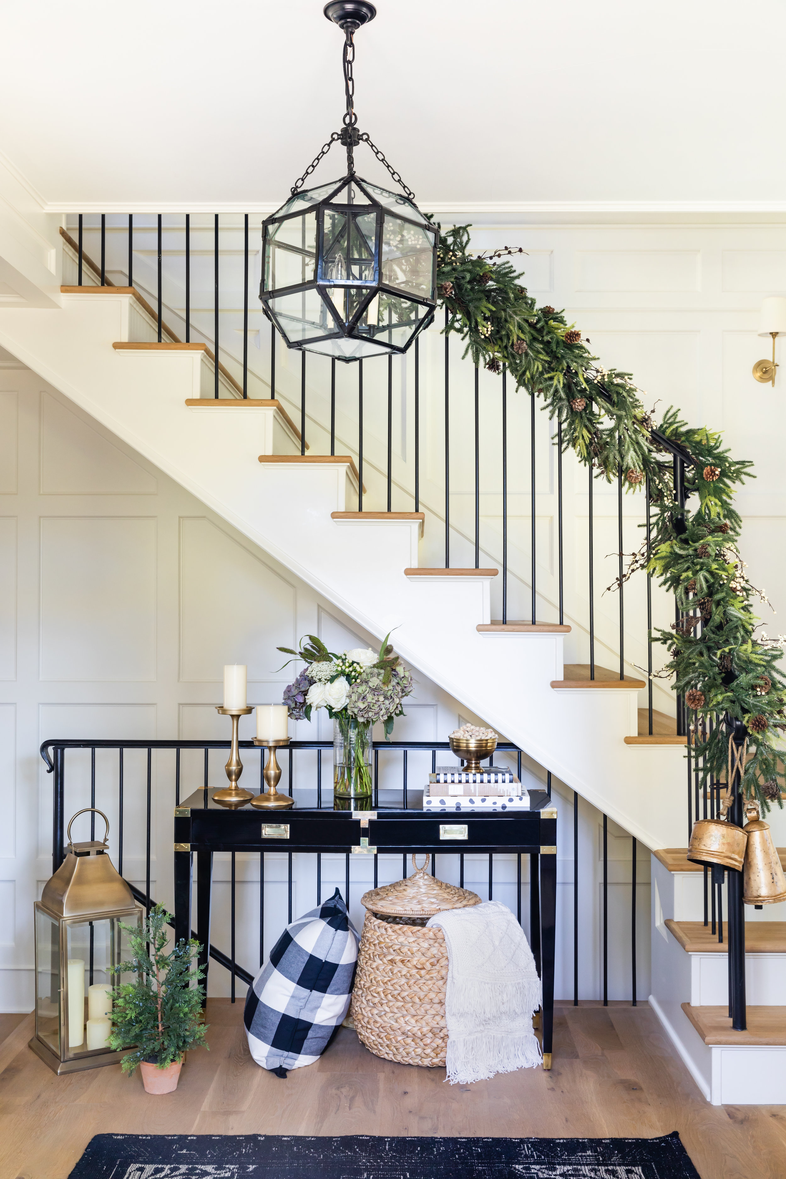Black and white contemporary entryway with Pottery Barn Christmas bells, garland on staircase, and brass lanterns.