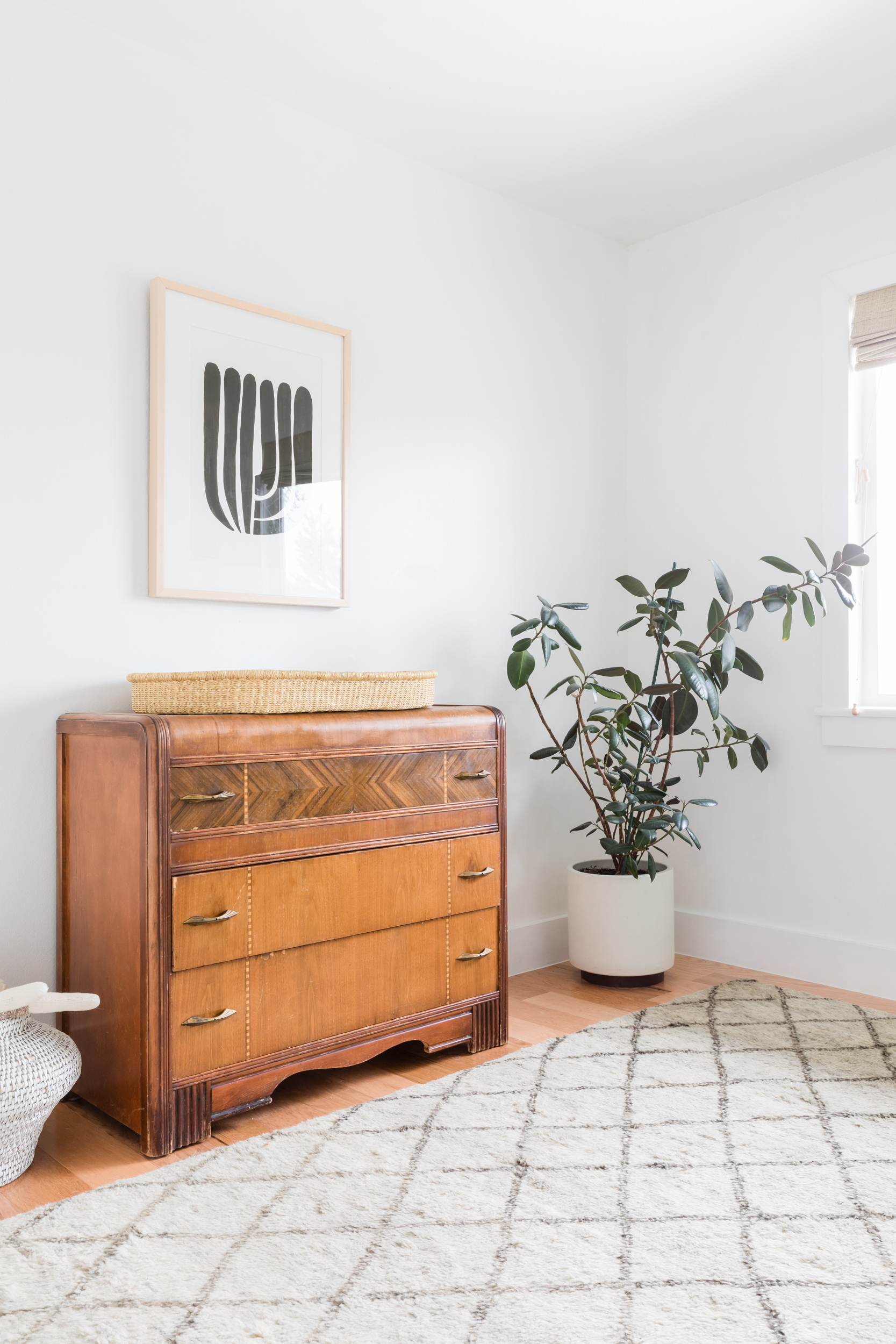Mid mod and minimalist nursery with white walls, potted rubber tree, and antique wooden dresser as changing table.