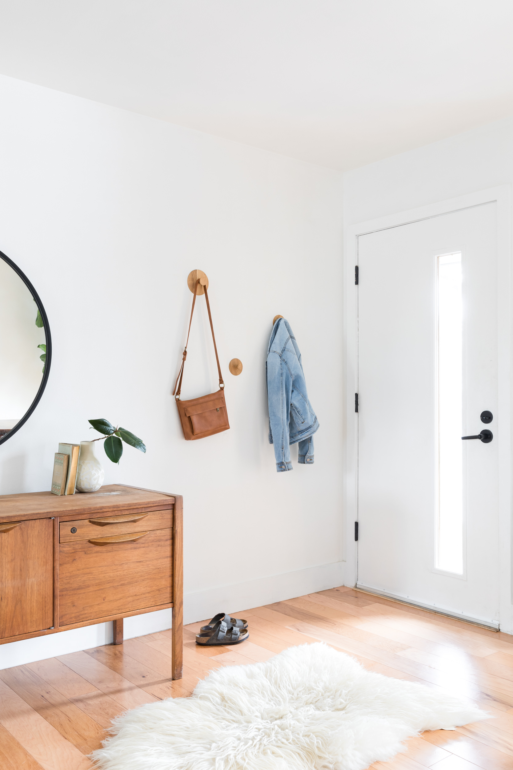 Mid mod entryway with purse and jean jacket hanging on wall and antique credenza and mirror.