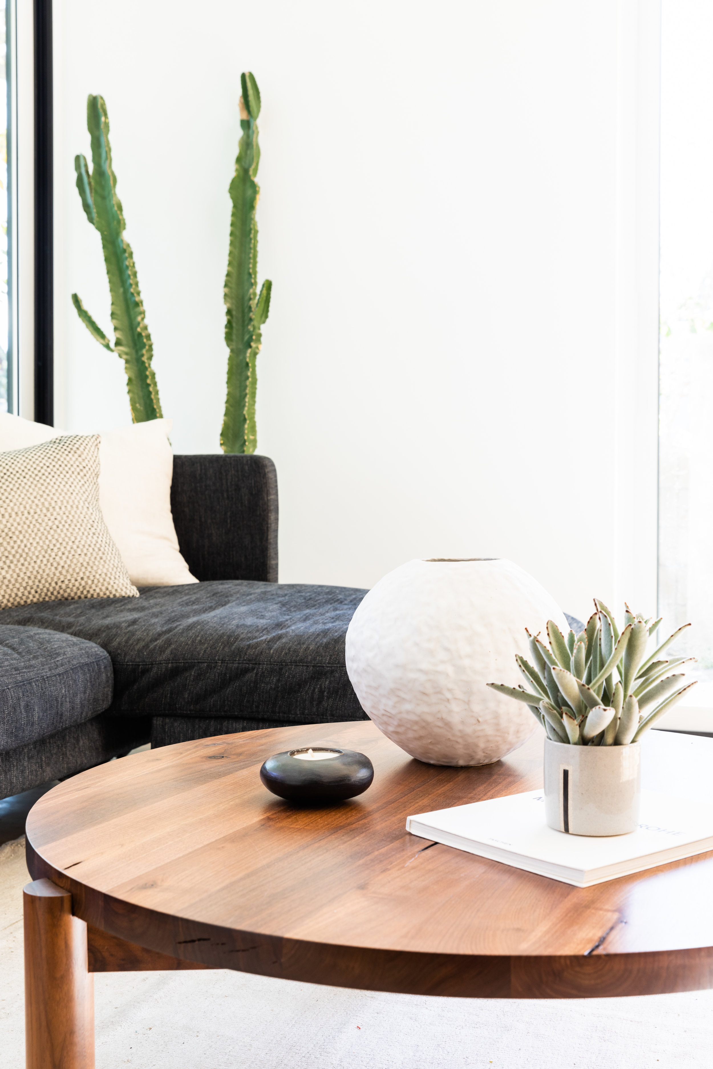 Round, wood coffee table in modern living room with ceramic vase, candle, and potted plant on it.