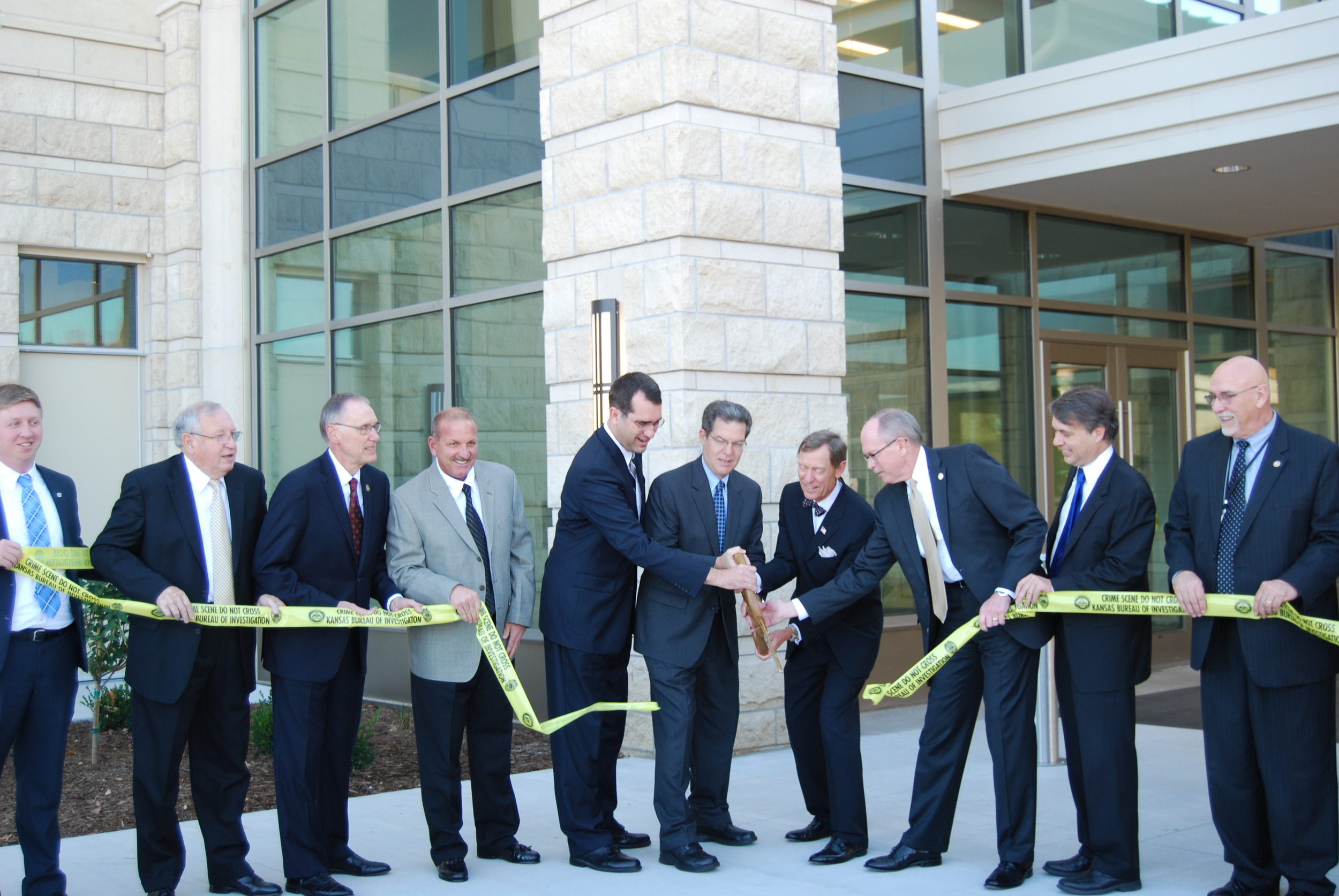 The project team and officials from the Kansas Bureau of Investigation and Washburn University perform a ribbon-cutting ceremony marking the debut of the new $55 million forensics lab.