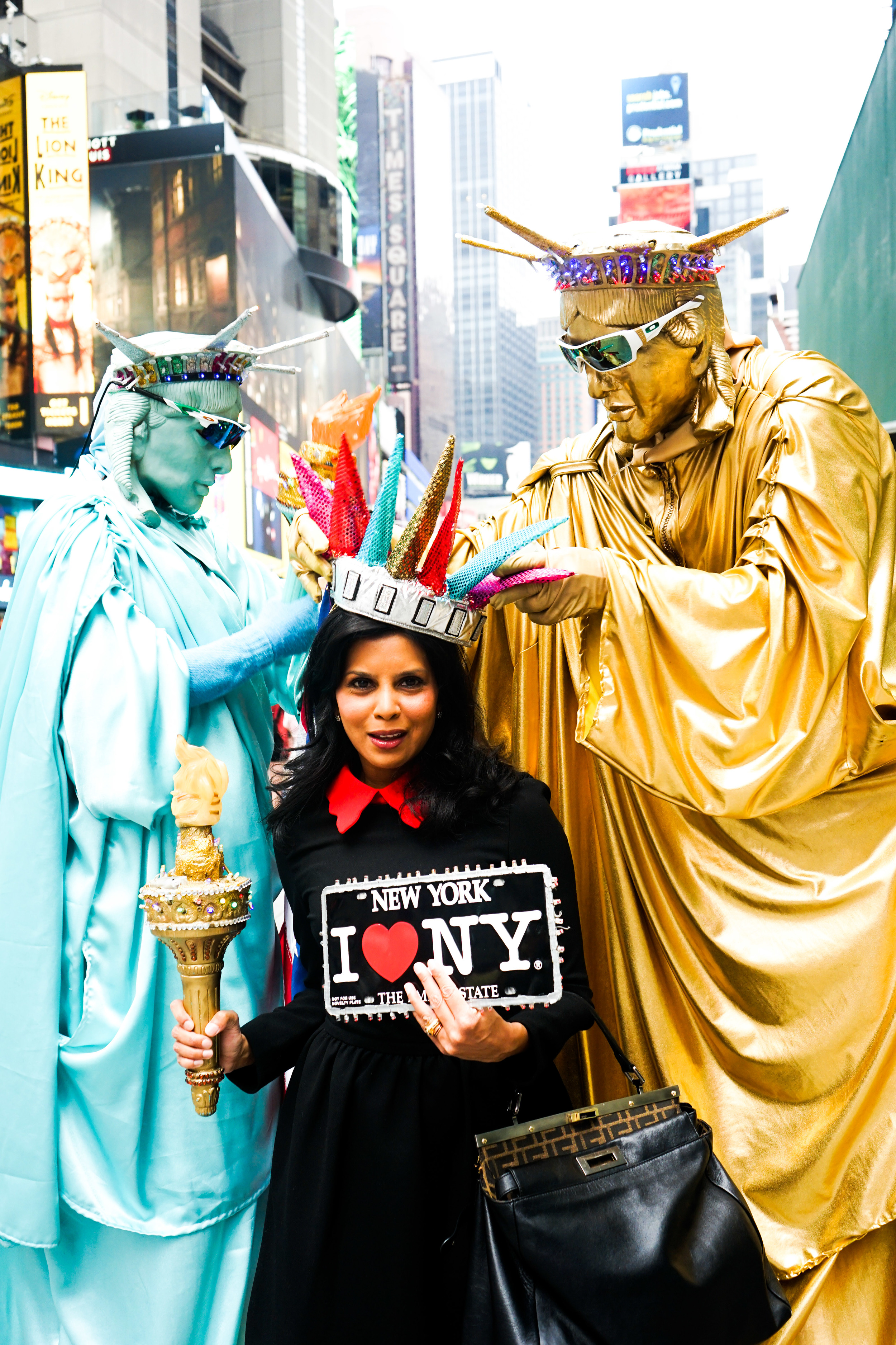 Hitha Herzog in Times Square wearing an inflatable Statue of Liberty crown, holding an inflatable Statue of Liberty Torch, surrounded by two street performers dressed as Statue of Liberties.
