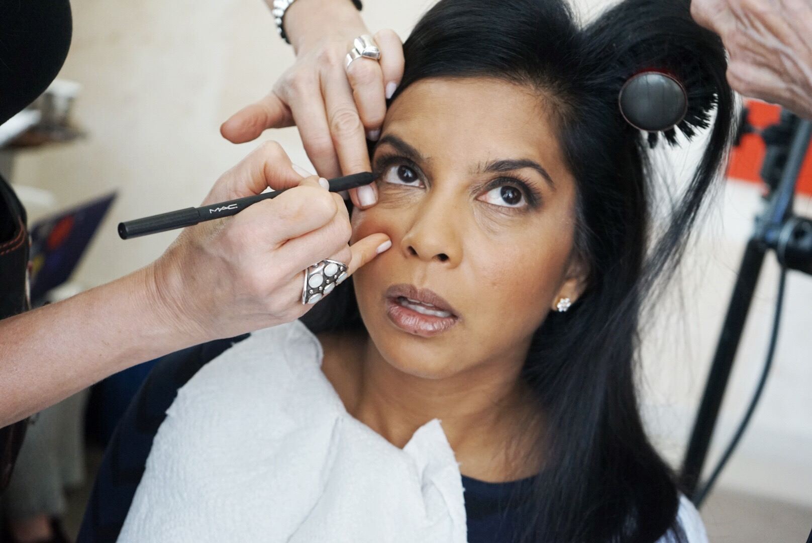 Hitha Herzog getting her eye rimmed with black eyeliner by a makeup artist.