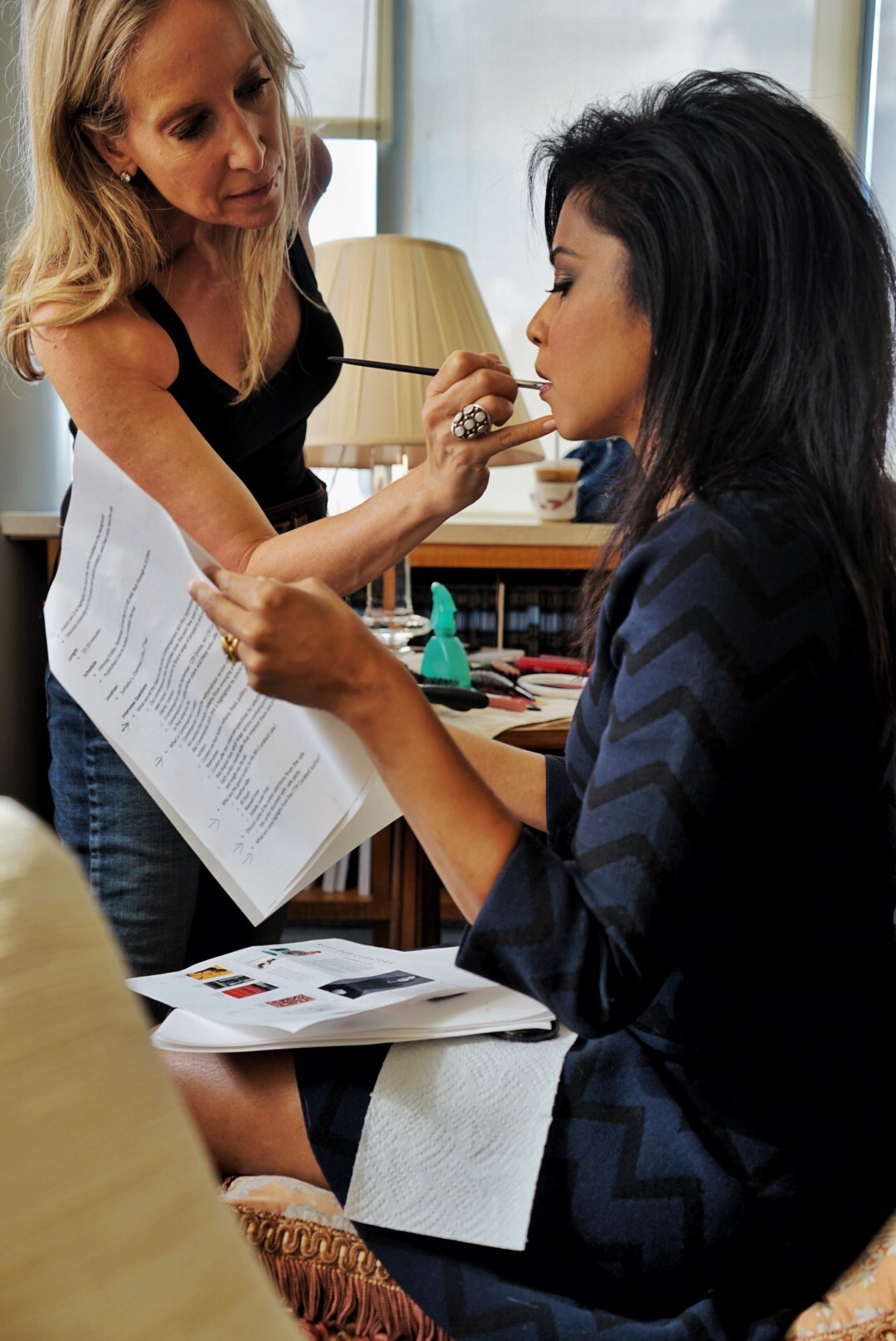 Hitha Herzog getting her makeup done by Laura Weinstein, while looking over notes for the Live show.