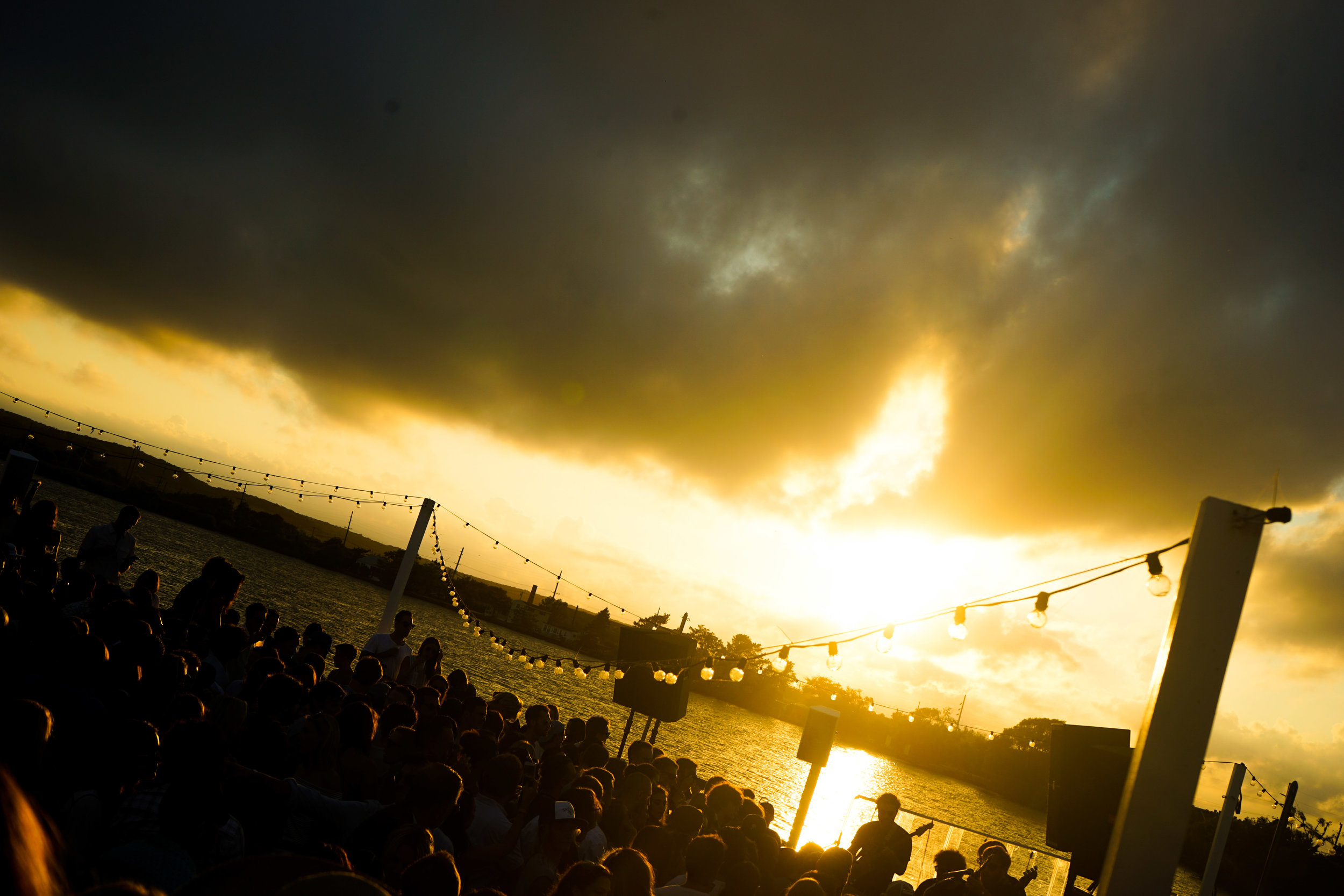 Overlooking a crowded party on the waterfront at sunset.