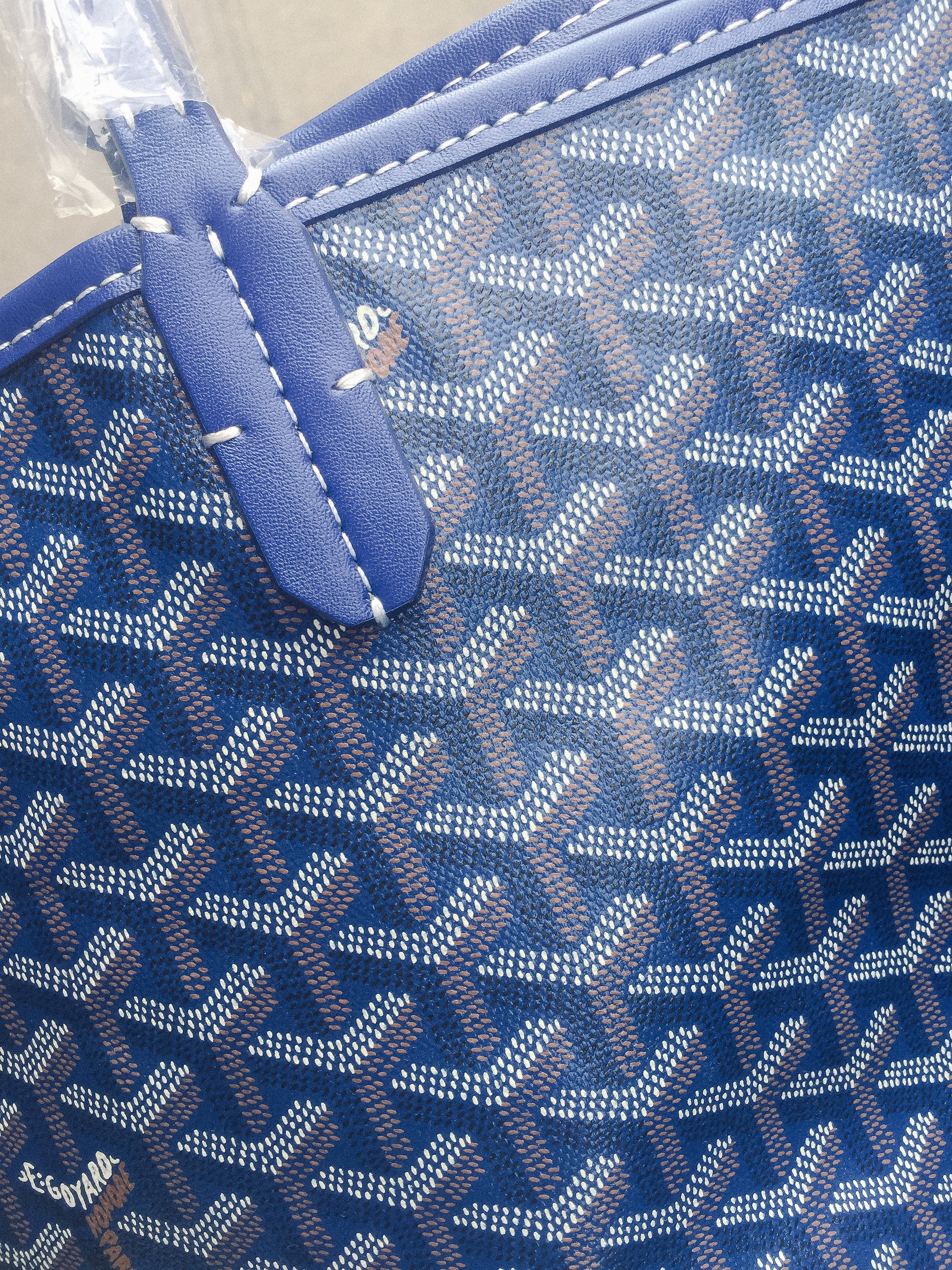 Aha! Indication #1 this is a fake Goyard bag: logo placement by the stitching. Real Goyard St. Louis bags do have white stiching on them. In fact, do you see where the logo gets cut off at the top left hand corner? Goyard bag patterns don't cut off the logo in that way.