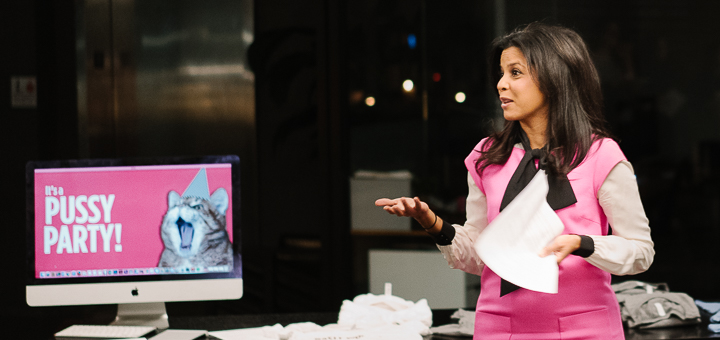 "Hitha Herzog in a pussy bow blouse in front of a computer saying ""It's a Pussy party!"" with a cat image."