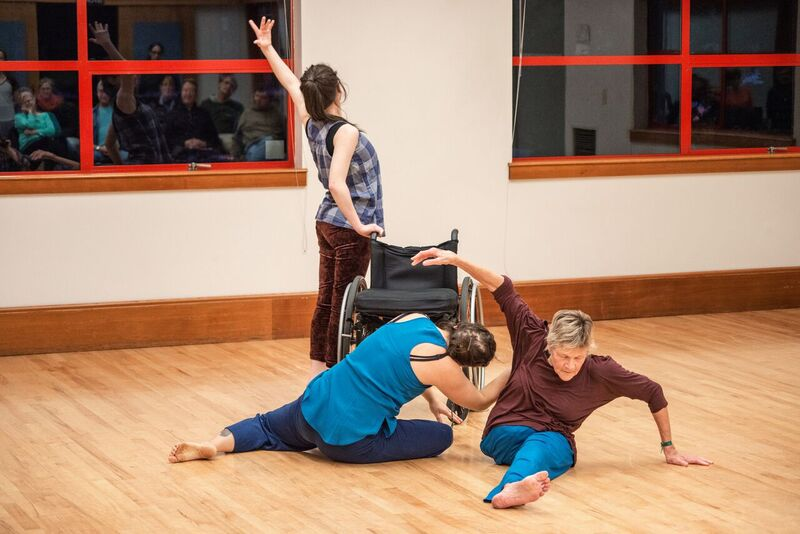image: three mixed ability dancers rehearsing. two are on the floor and one is leaning on a wheelchair.