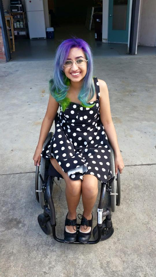 Photo of Roya Bhargava,. She is a young person of color sitting in a wheelchair. She has purple and green hair, is wearing glasses and a polka dot dress, and is smiling at the camera.