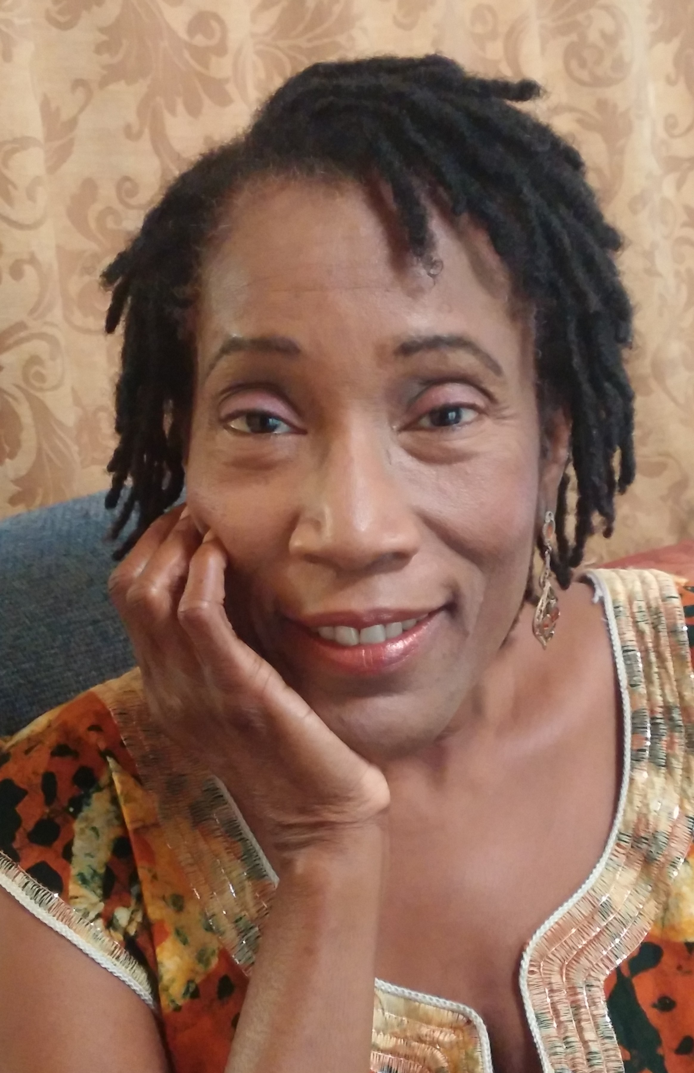 Photo of Muitma Imanii. She is an african American woman with hair in short Locks. She is wearing earrings, a brown shirt, and smiles as she leans on one hand.