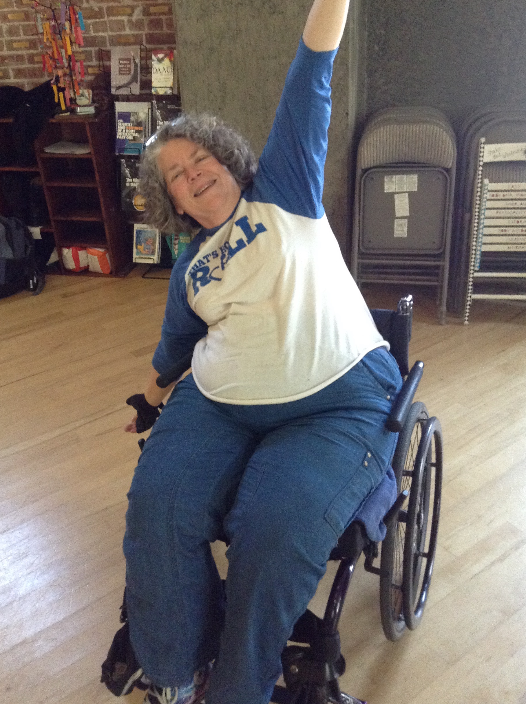 Photo of Tara Ayres. She is a white wheelchair user with graying curly hair. she sits in her wheelchair, stretching her arms out, and smiling at the camera. she is wearing a white t shirt and blue pants.