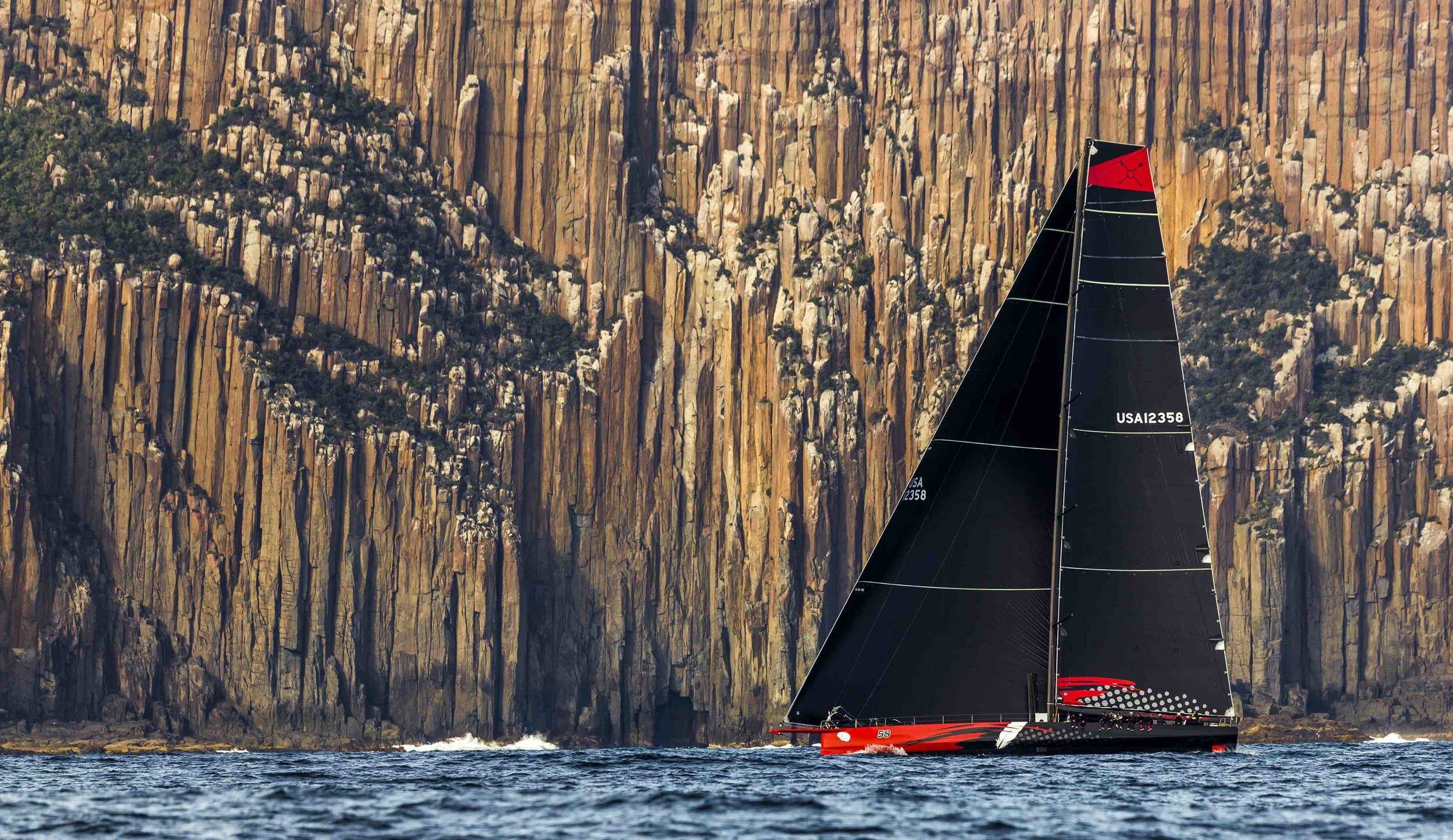 Line honours winner Comanche passing the Organ Pipes along the Tasmanian Coast in 2015 Sydney Hobart Race