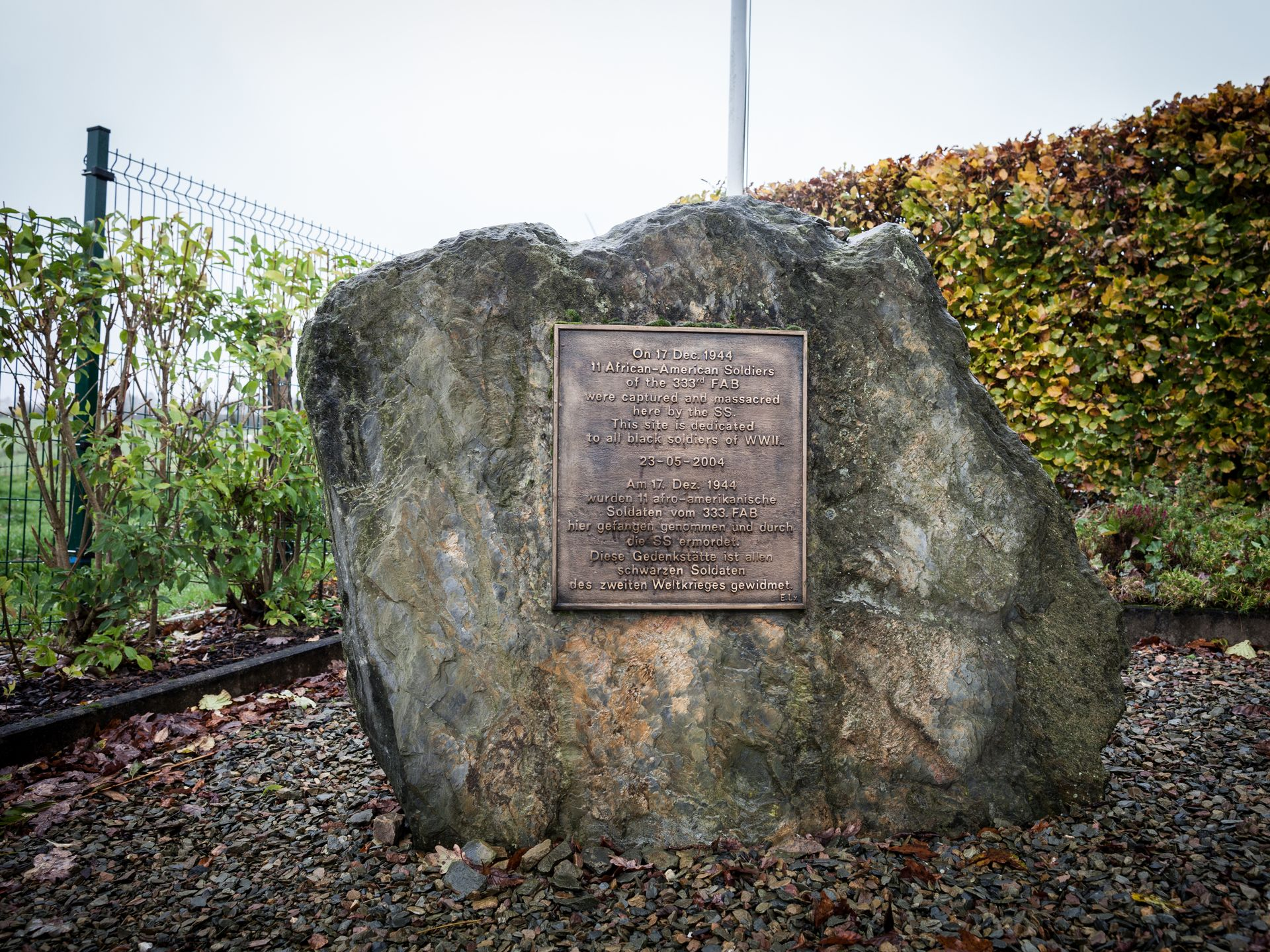 """The inscription reads, """"On 17 Dec 1944, 11 African-American Soldiers of the 333rd FAB were captured and massacred here by the SS. This site is dedicated to all black soldiers of WWII"""""""