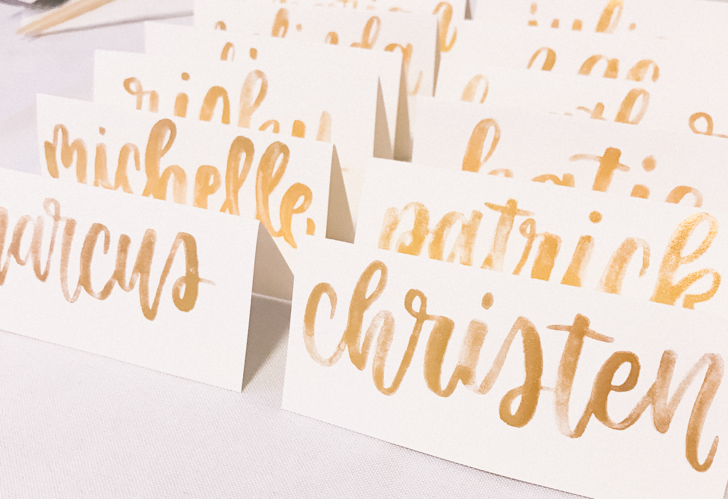 Handlettered gold place cards for our guests!