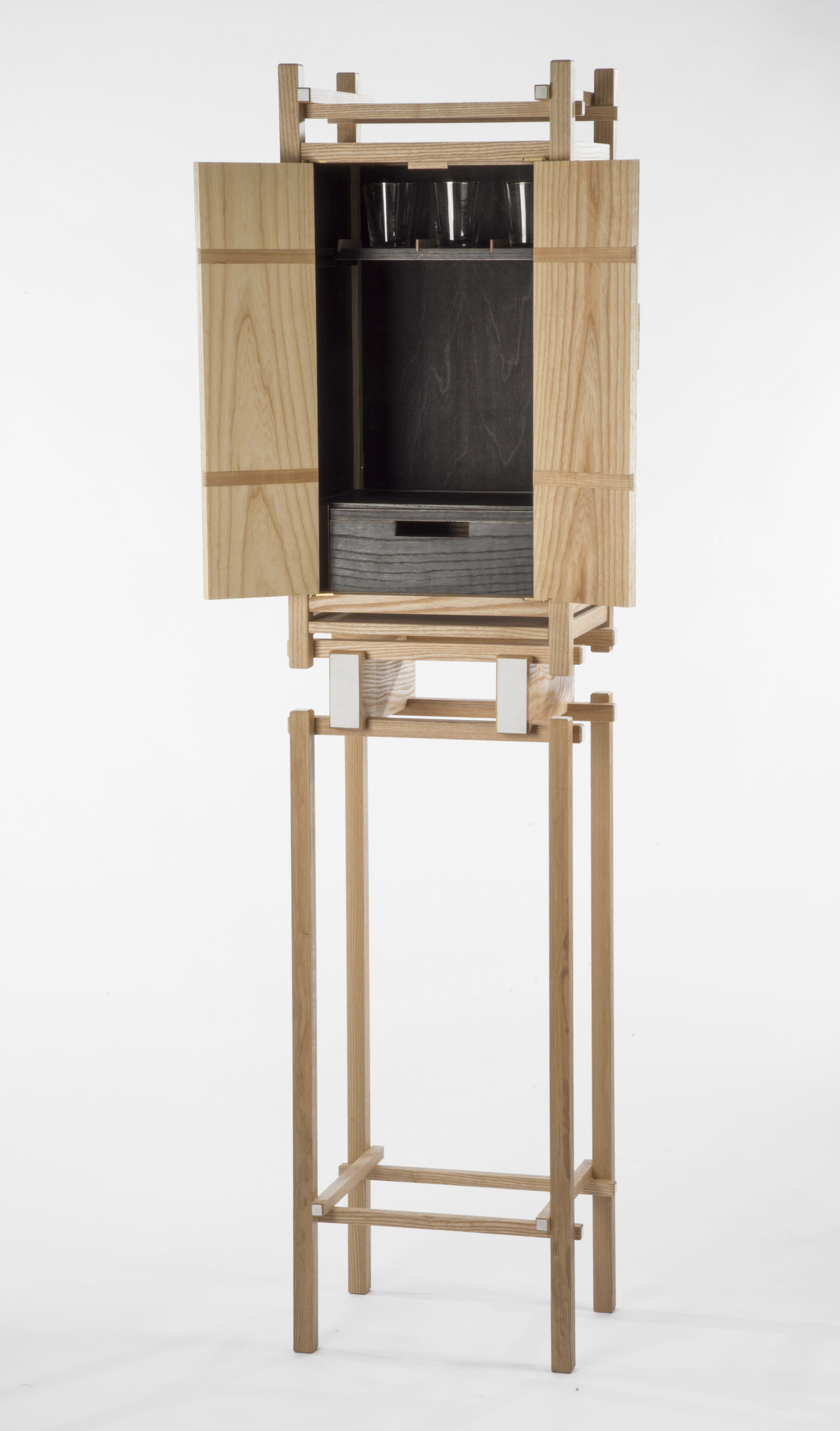 """Liquor Cabinet is designed within the constraints of a three part construction system: two sizes of square stock, floating panels, and pinned butt joints. The use of square stock and panels allow for attention to be placed on the intersecting horizontal and vertical lines.     Materials: Ash wood  H 72"""" x L 17"""" x W 13"""""""