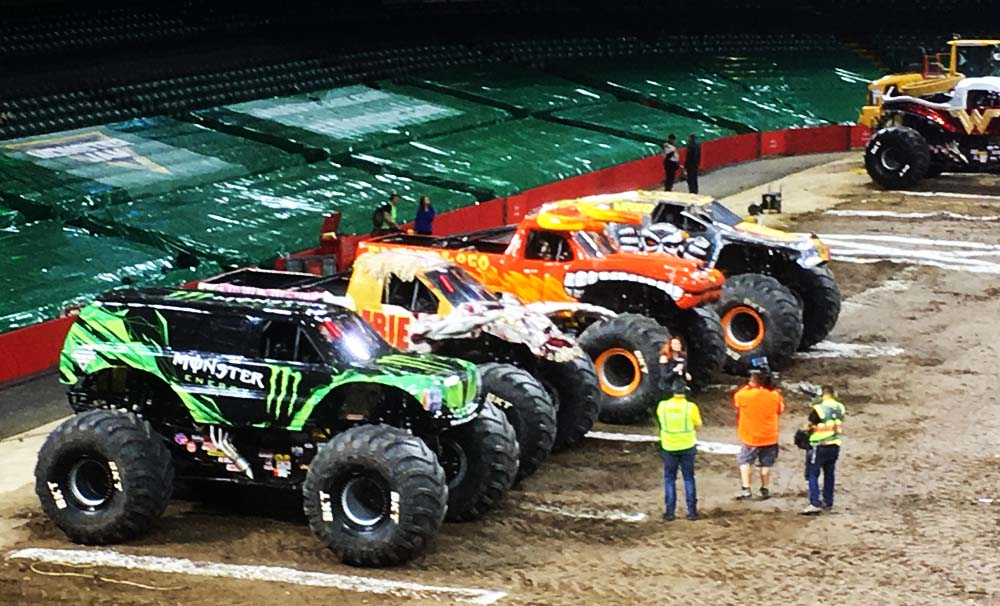 Monster Jam trucks line-up in the interval as the video-team record links in Cardiff.