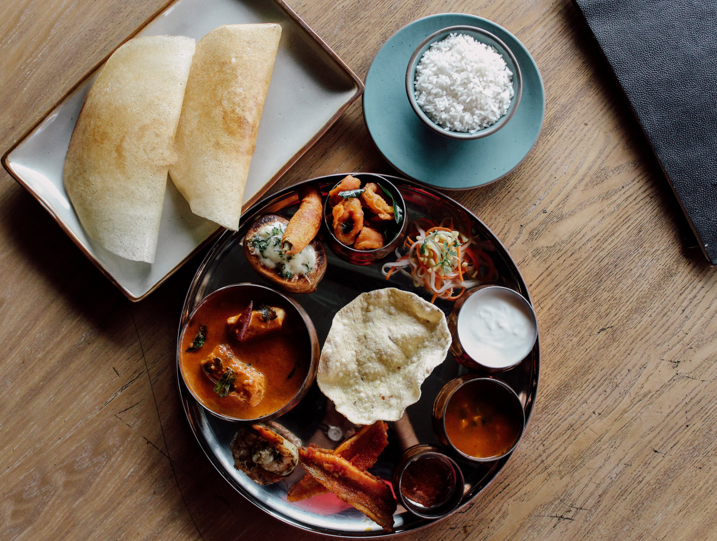 The table, the thali, the sides, and the menu within arm's reach. Hi, perfect setting.
