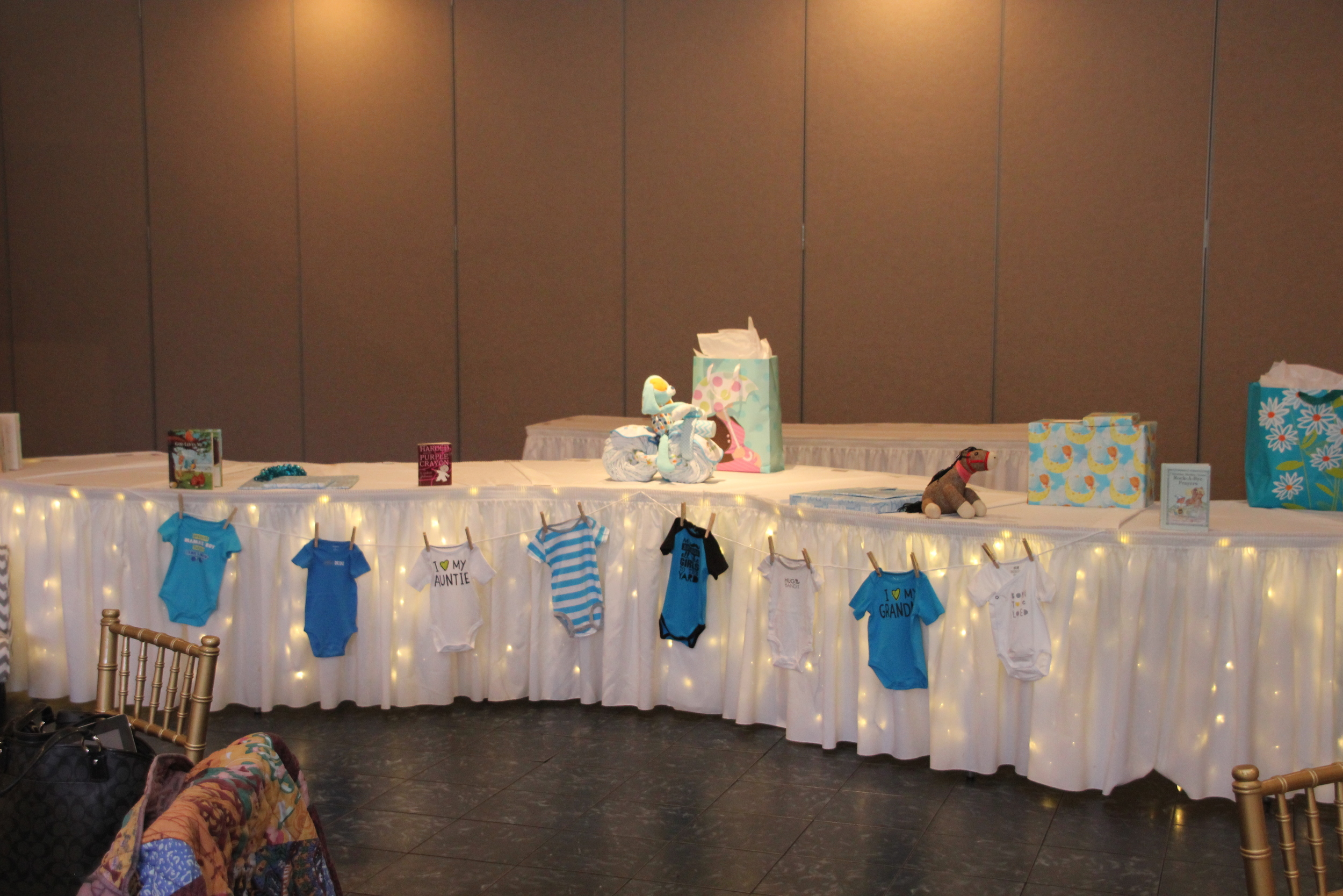 Our serpentine gift table is perfect for some little onesies on the clothesline.