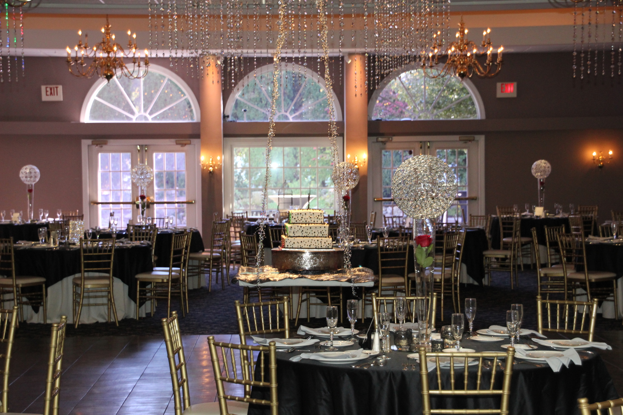 Aces and Eights ceiling with hanging cake and Black Satin tablecloths