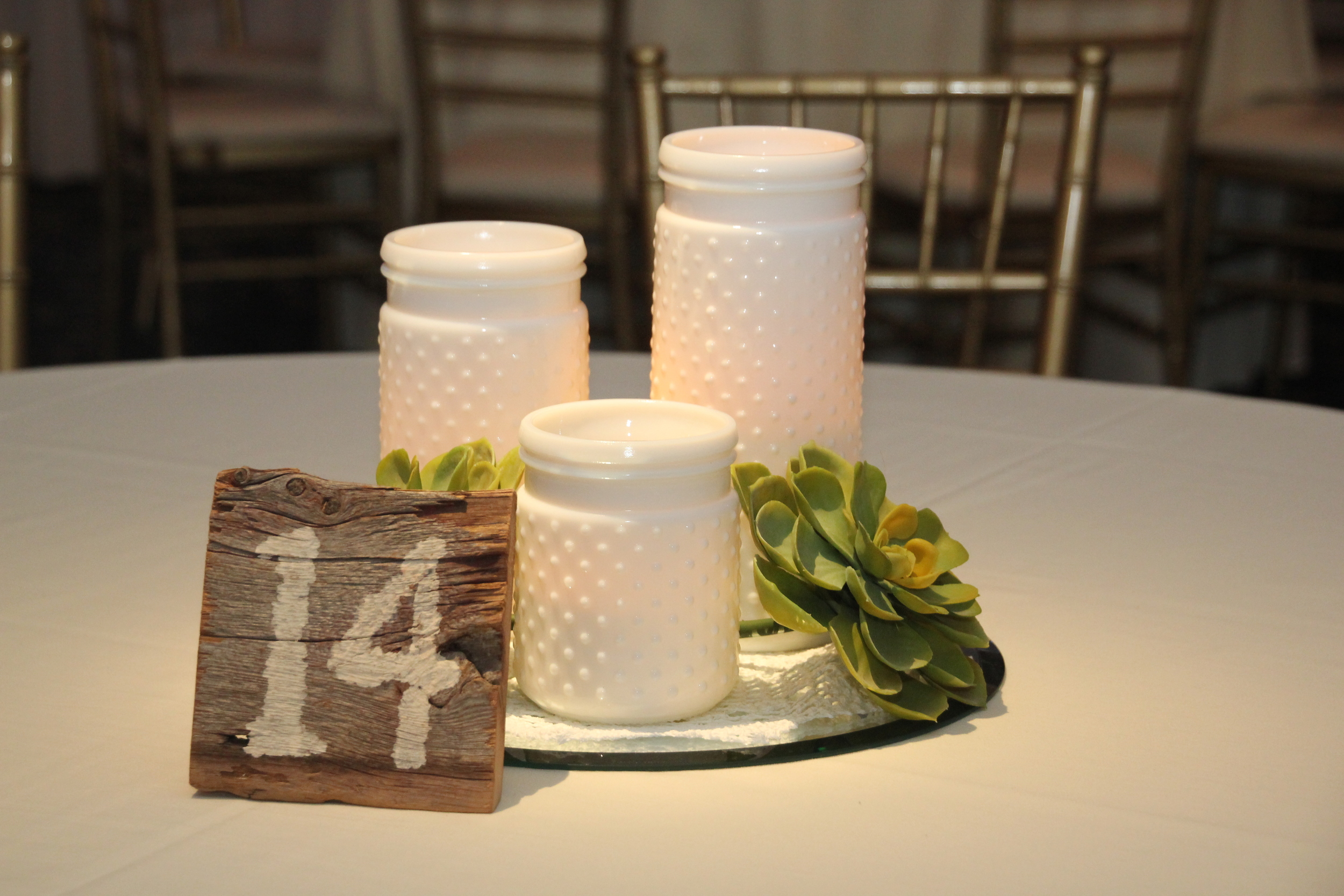 White hobnail cylinders on silver charger with wooden table numbers