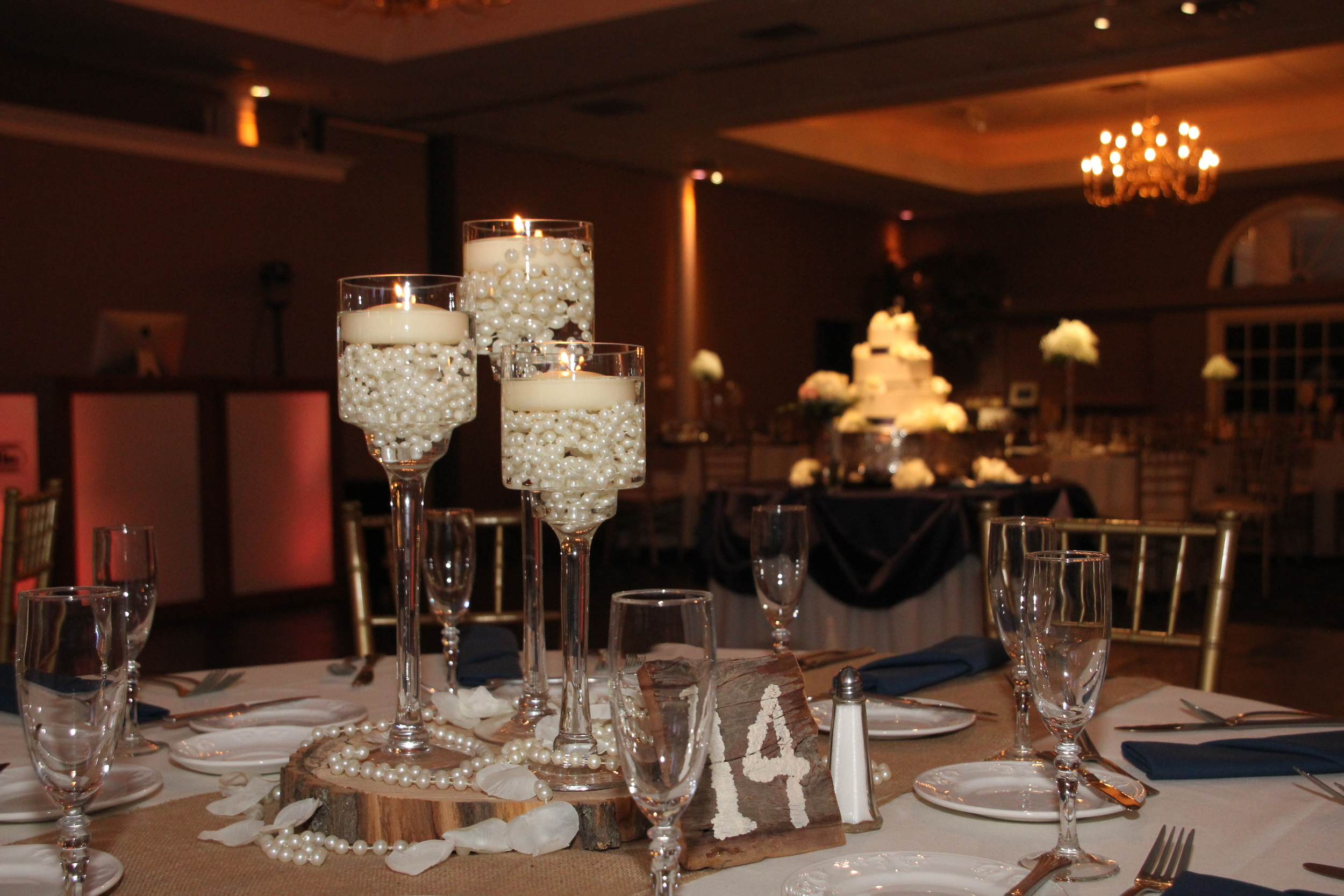 Three footed cylinder set with ivory pearls on wood charger with wood table numbers and ivory floating candles
