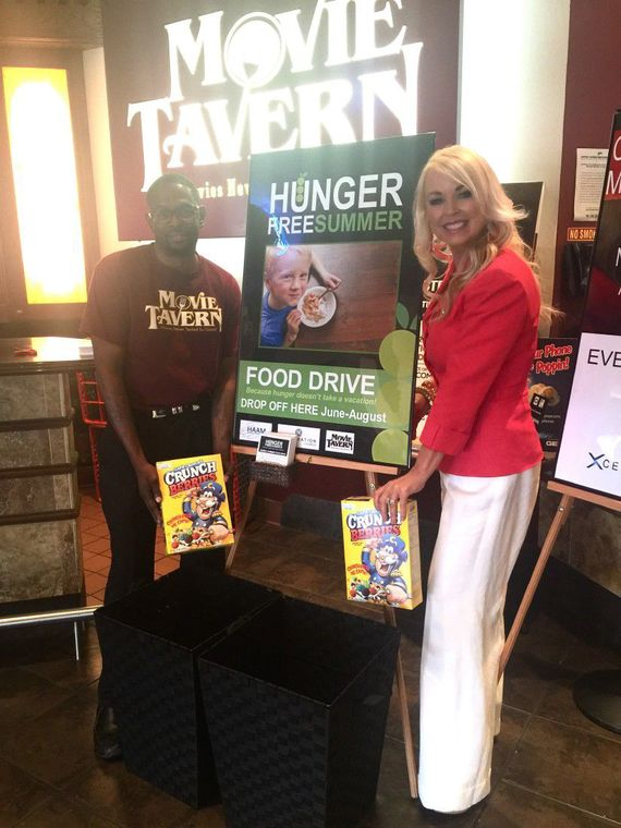 Xceleration Church Pastor Sally Davis (right) poses with Humble Movie Tavern assistant manager Michael Meade (left) by their Hunger Free Summer Food Drive poster.
