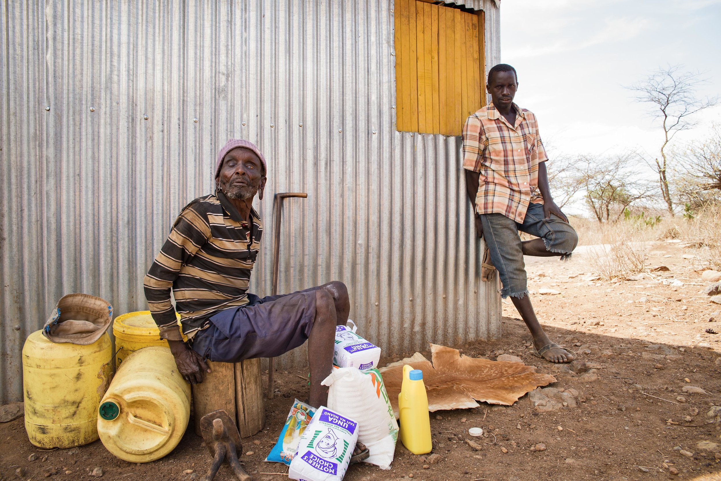 """Cherutich Kigen and his son sit outside his home in Baringo County, Kenya. """"There is a lack of water and lack of food. I'm unable to meet my basic needs,"""" he said."""