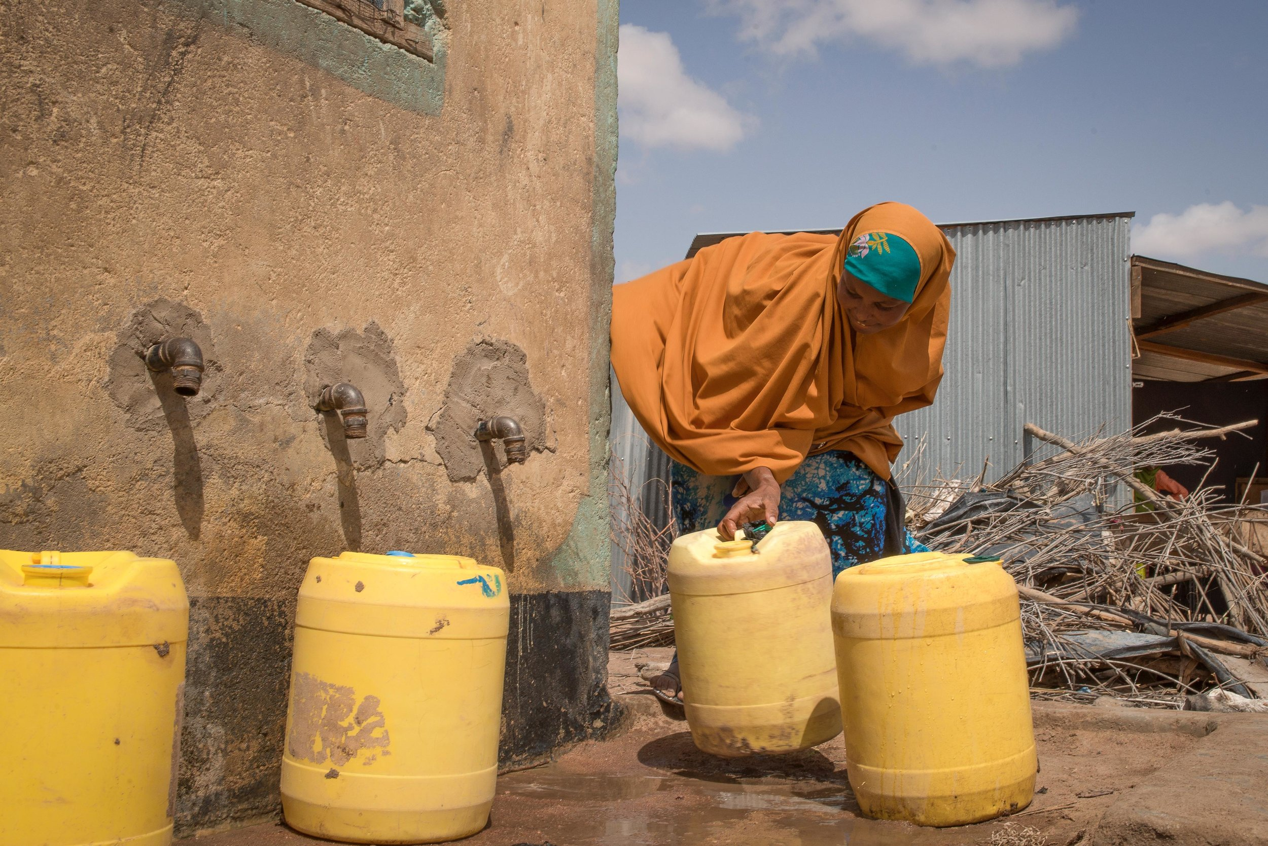A woman uses her water credit, which is stored in a small, plastic token, to buy water from a Water ATM in Hadado, Kenya.
