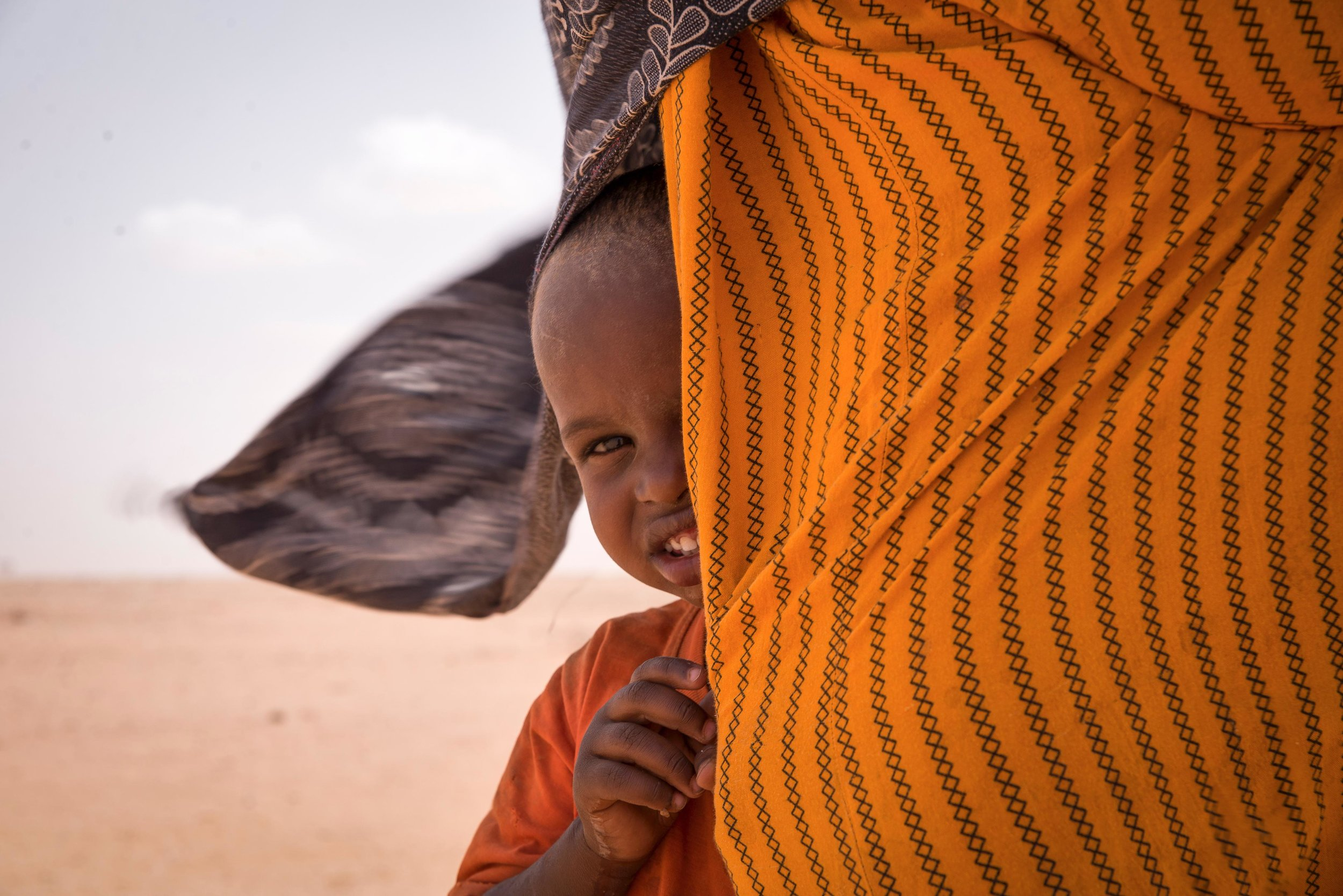 A boy hides behind his mother's dress during a sandstorm in a remote village in Wajir County, Northern Kenya.