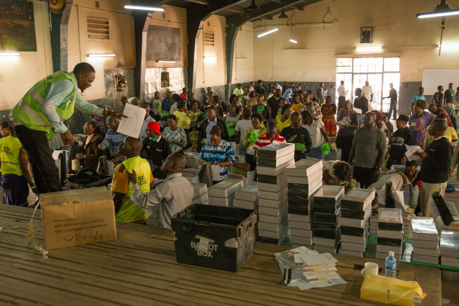 Officials with Kenya's Independent Electoral and Boundaries Commission distribute ballots and vote tallying forms to polling station officers before Tuesday's presidential election. Katie G. Nelson
