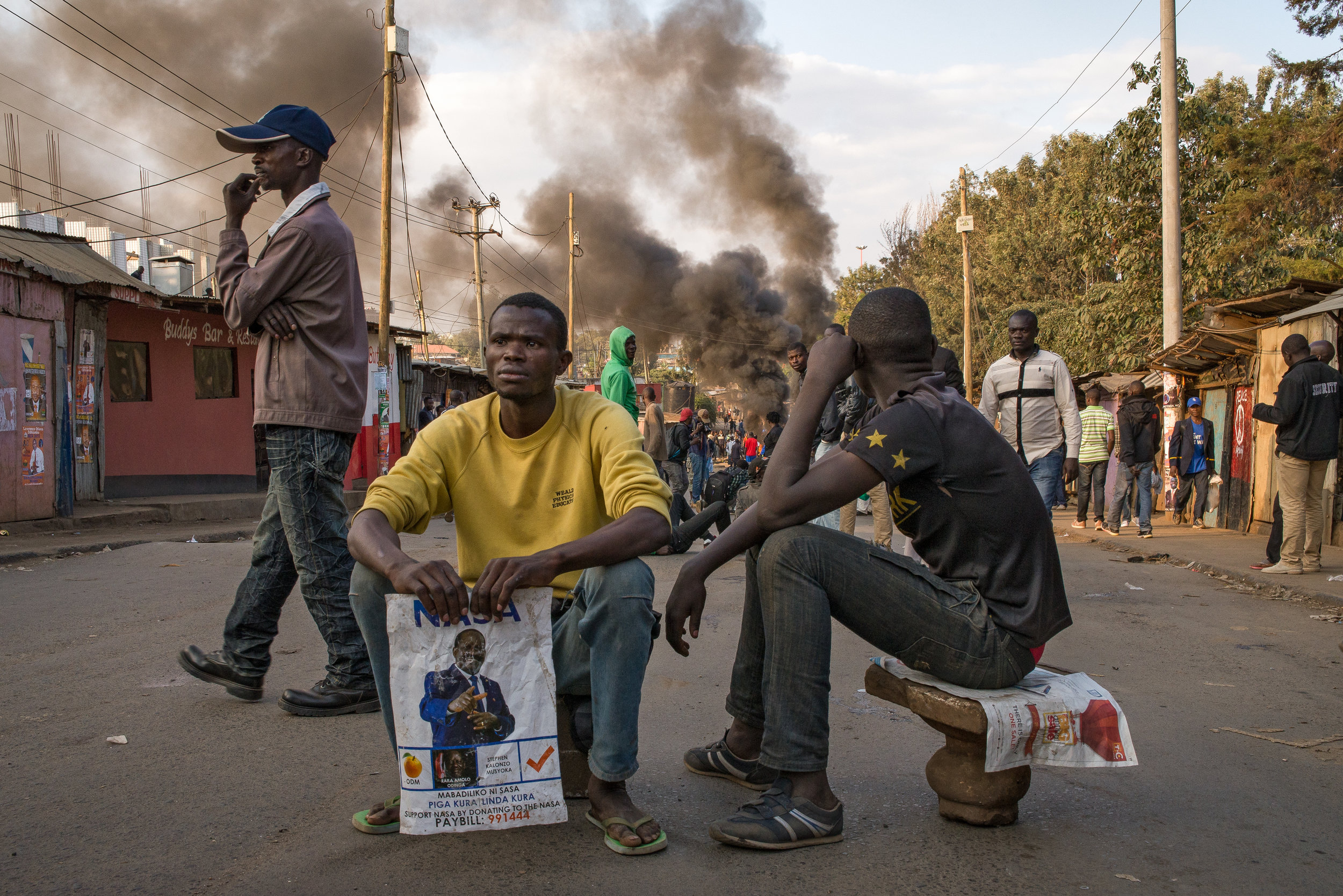 Men watch demonstrators light tires on fire in Nairobi's informal settlement of Kibera. The demonstration quickly turned violent as demonstrators armed themselves with stones and clubs bearing nails Wednesday evening. Credit:Katie G. Nelson/PRI