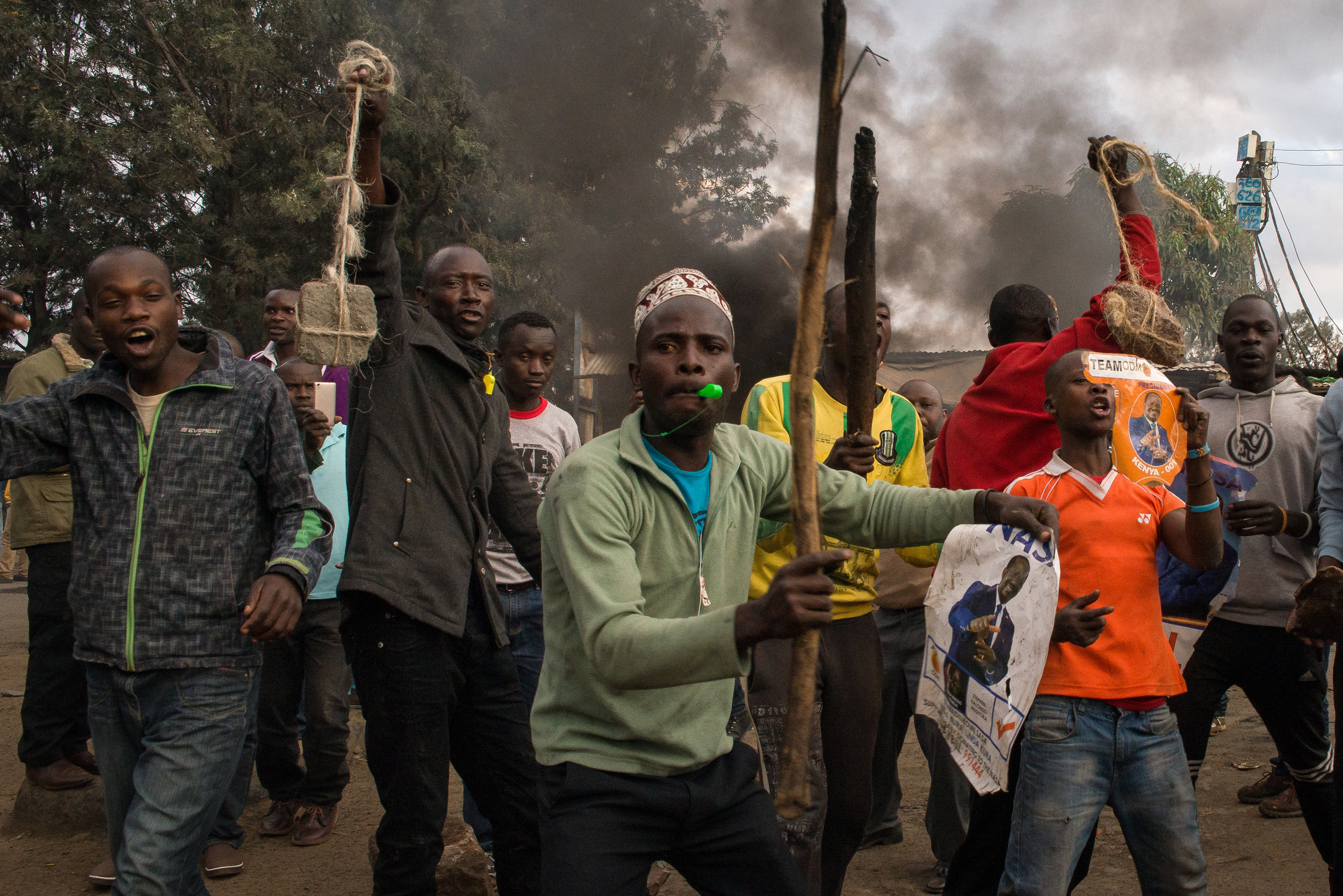 Men arm themselves with stones and clubs before clashing with residents in Kibera, an informal settlement in Nairobi, Kenya. The men supported presidential candidate Raila Odinga of the National Super Alliance over current President Uhuru Kenyatta. Credit:Katie G. Nelson/PRI