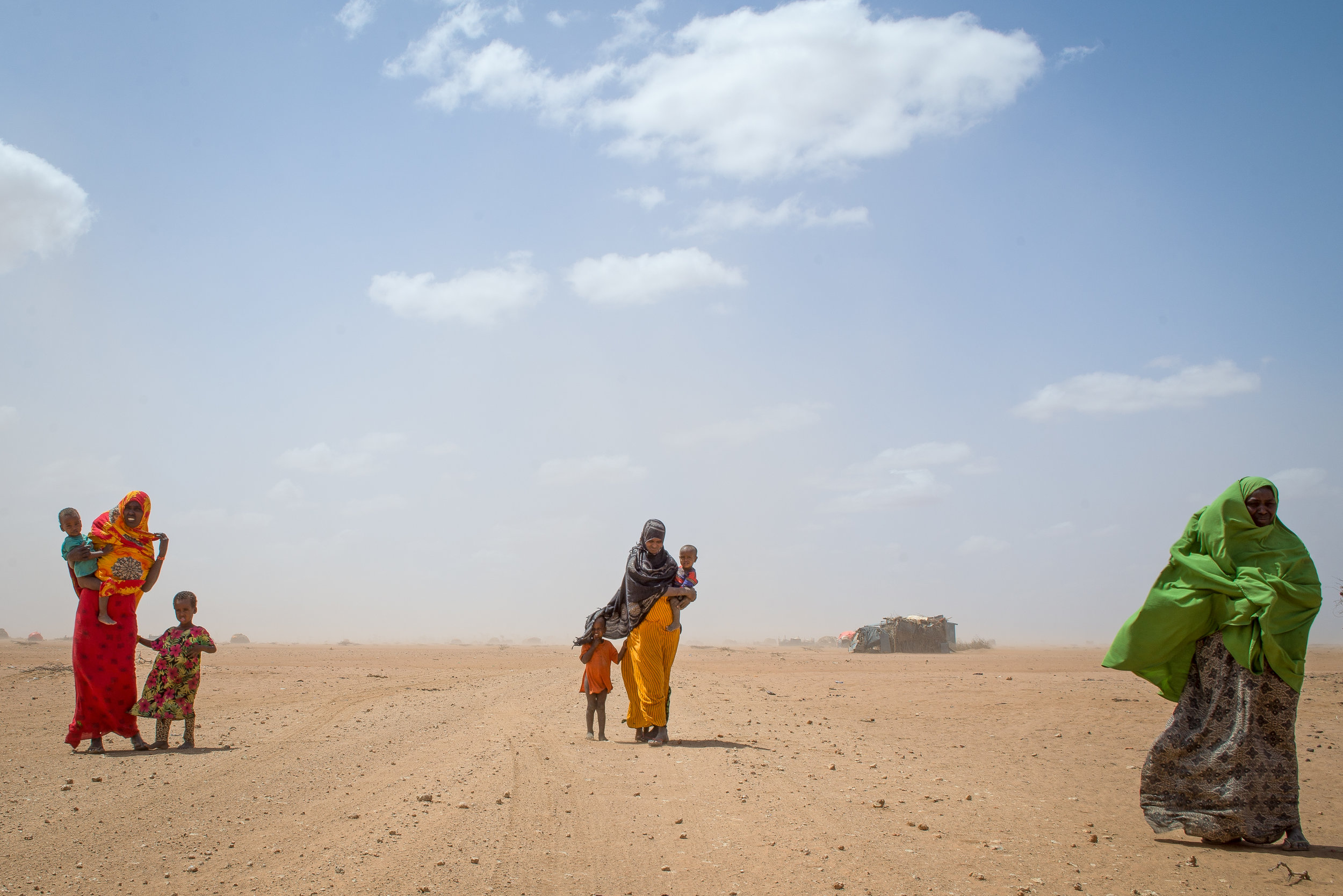 Women carry their children through a sandstorm in a remote village of Wajir County, Kenya.