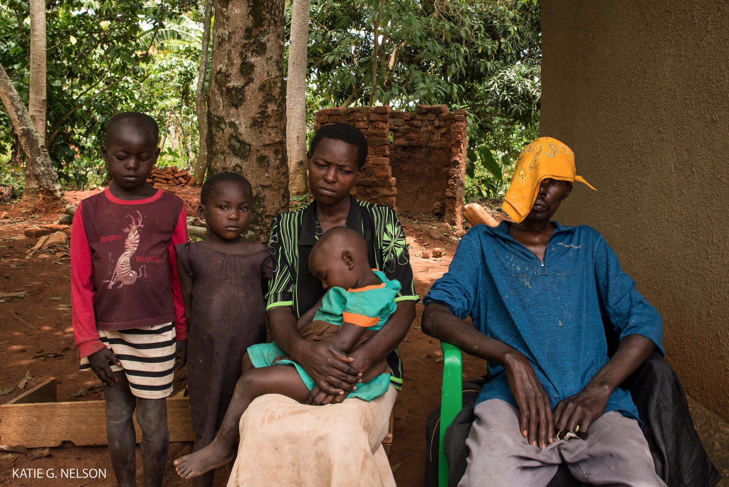 Gali, his wife and three of his seven children sit outside their home in southeastern Uganda.