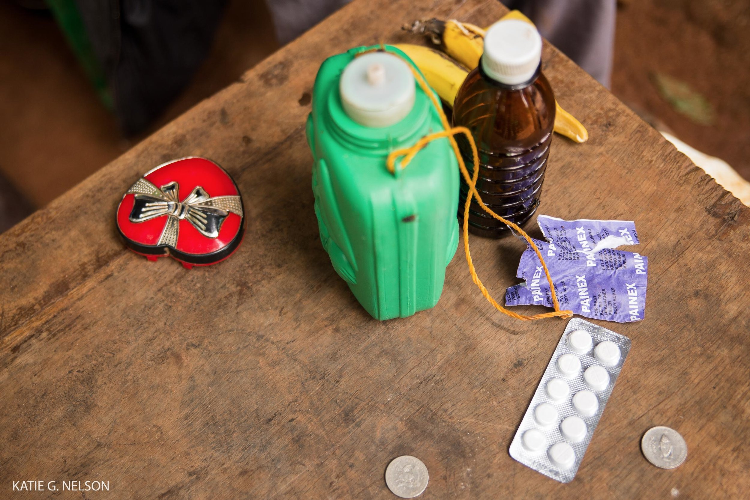 A table holding Gali's medication and a red pocket mirror.