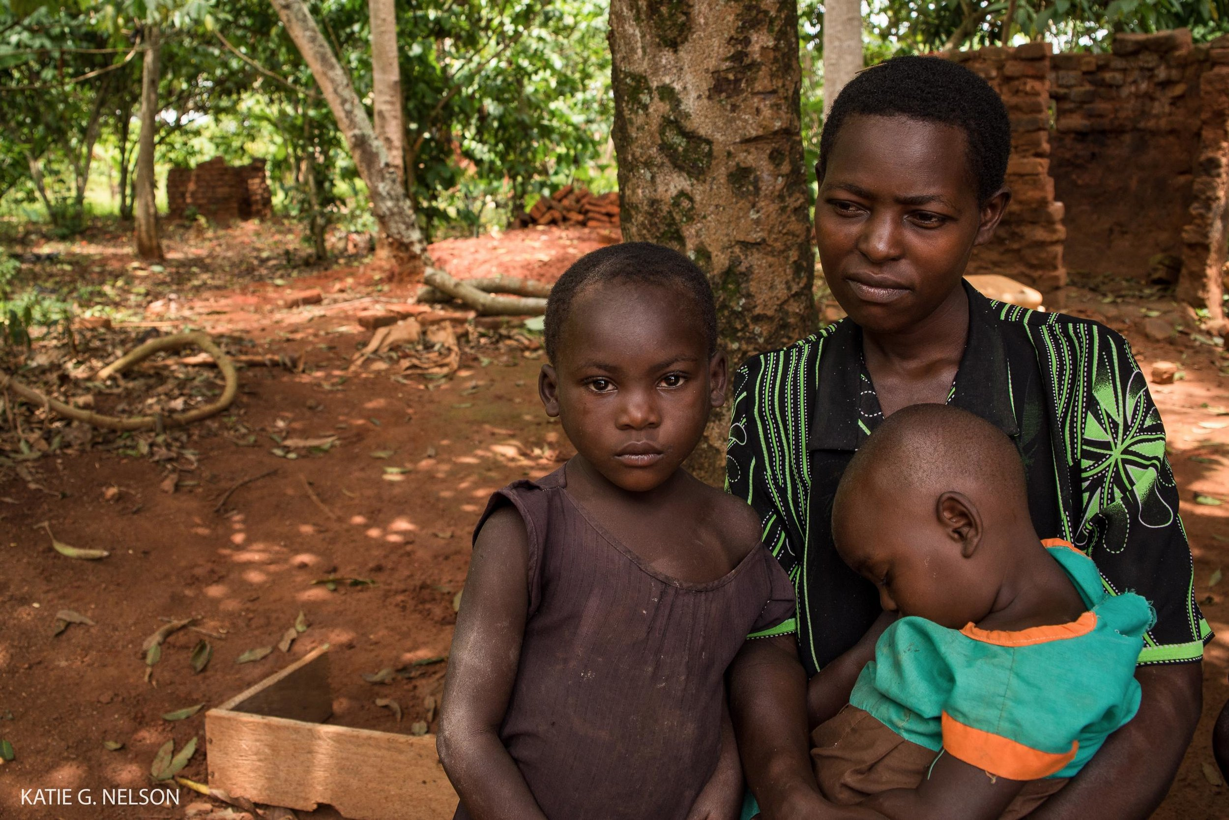 Gali's wife, Faridha Kadondi, 34, sits with her two daughters outside their home in southeastern Uganda.