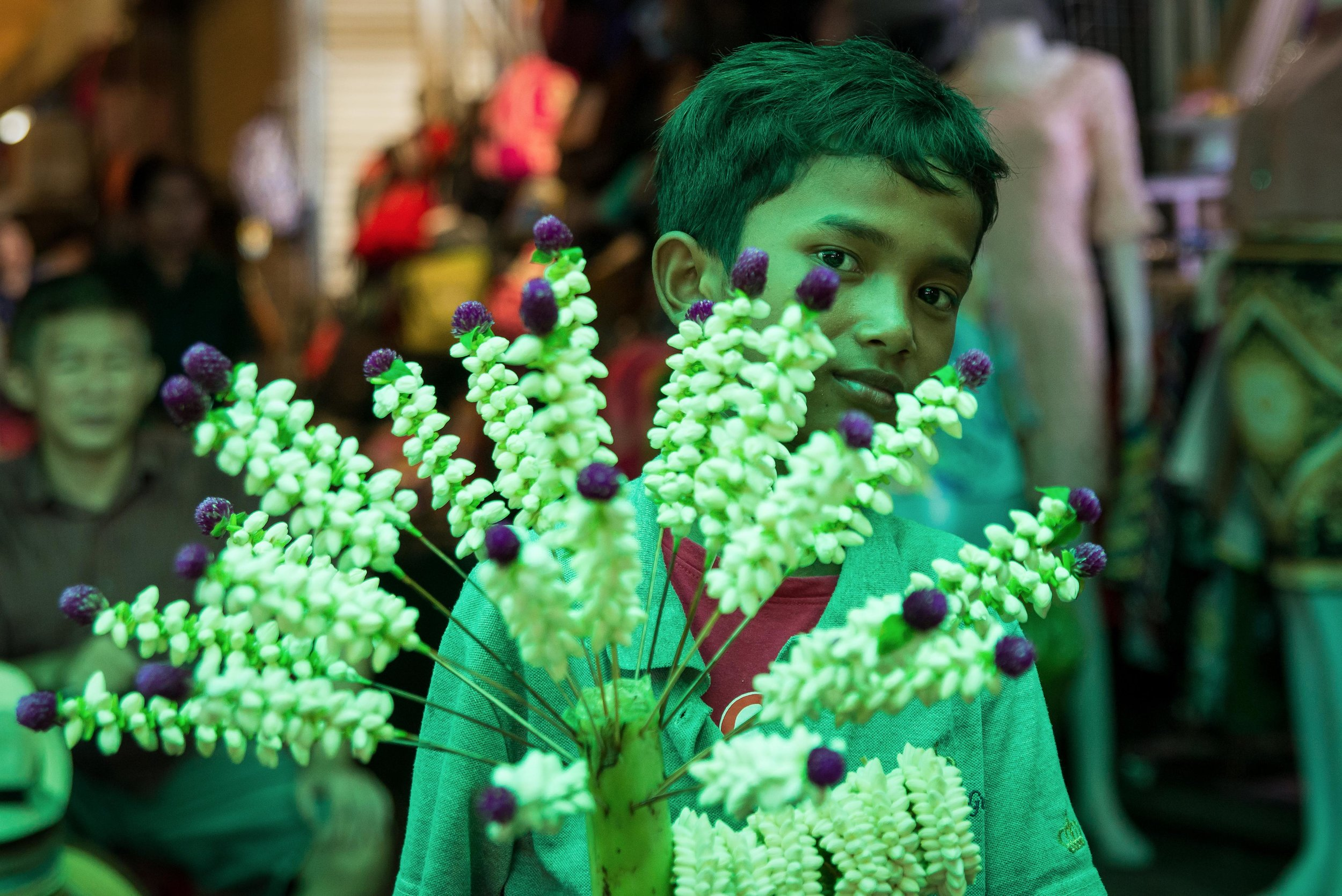 A boy holds a bouquet of flowers in Bangkok, Thailand. April 2016.