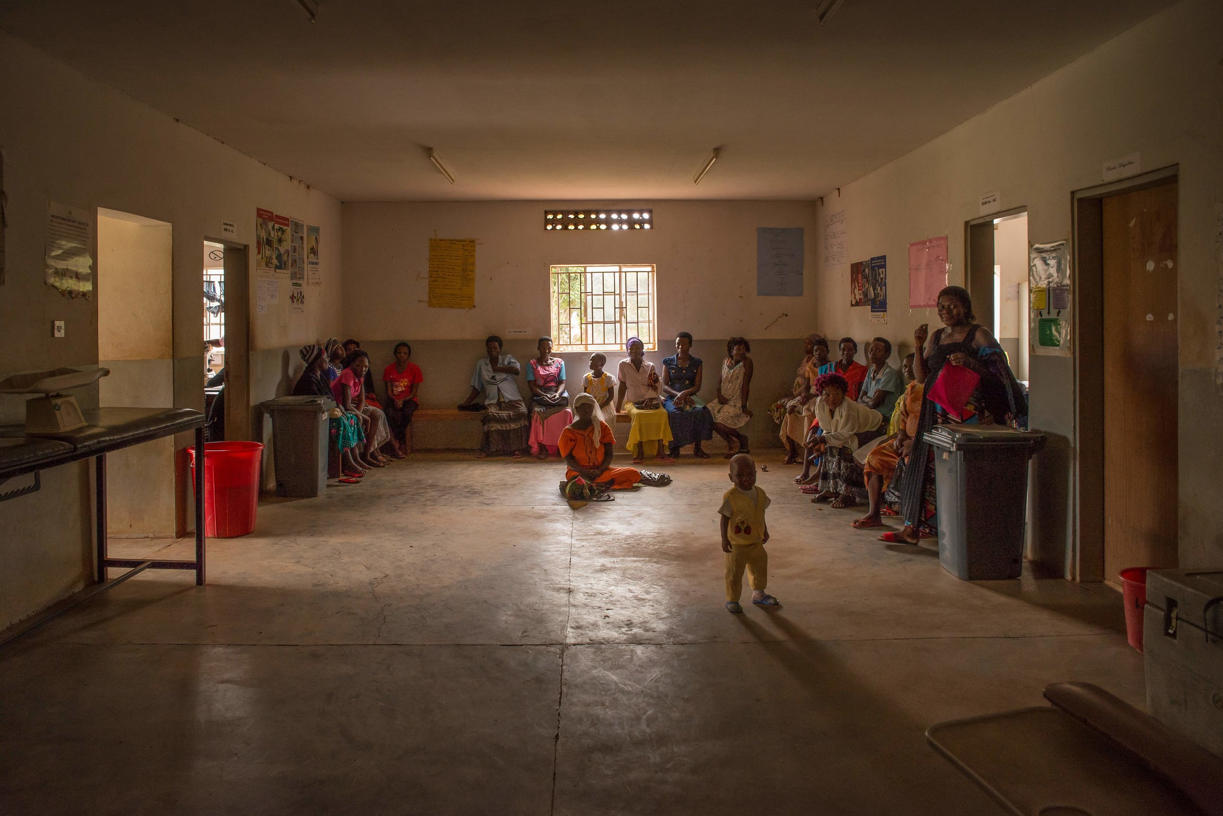 Patients wait in the lobby of Wabulungu Health Clinic III in Uganda. More rest on the grassy field outside.This clinic, along with a others in the area, have experienced shortages or complete stock-outs of HIV medication since November 2017 – some lasting as long as one or two months at a time. Photo: PRI/Katie G. Nelson