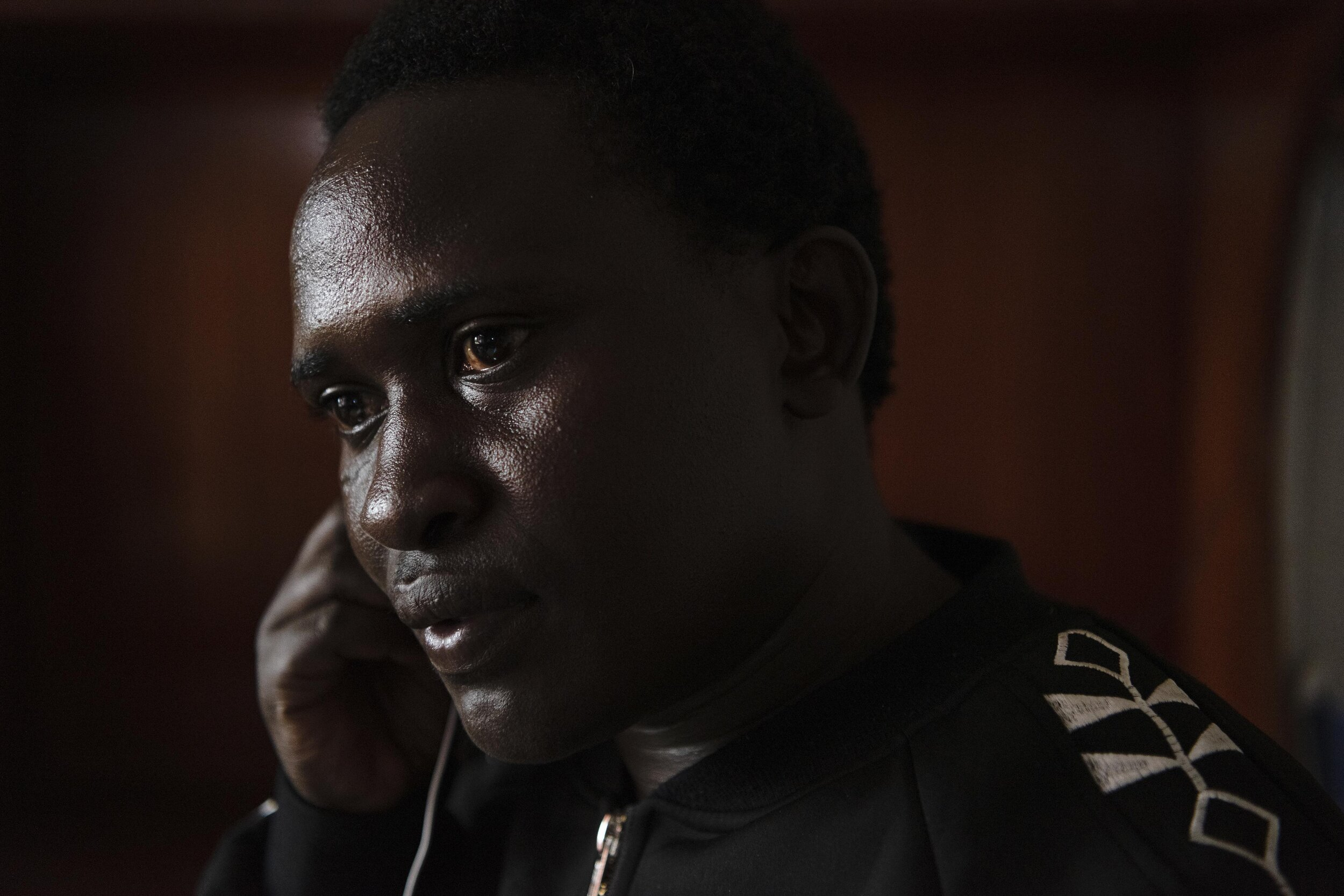 Kwaboka Kibagendi, the executive director of Jinsiangu, works at his desk in an intersex, transgender and gender-nonconforming safehouse in Nairobi, Kenya. Public Radio International, 2019.