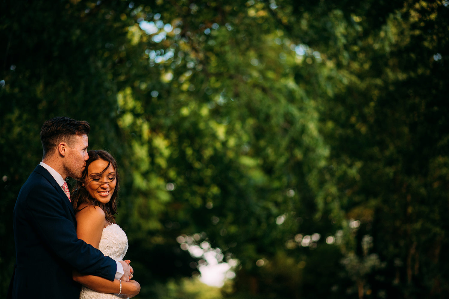 colour photo of bride and groom hugging