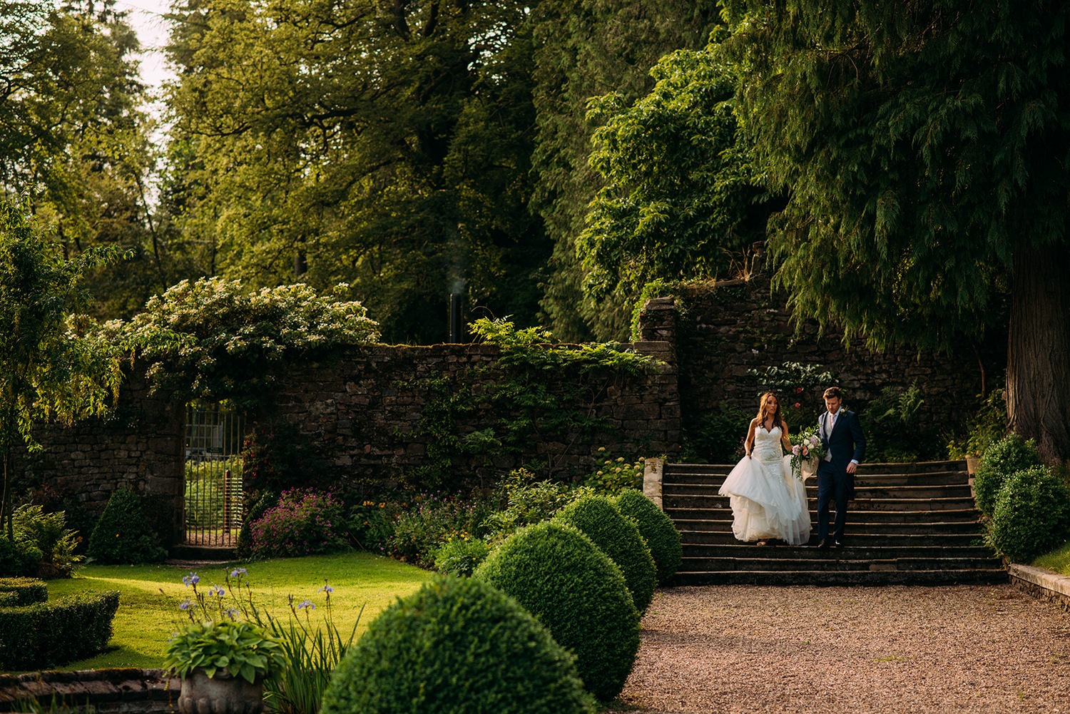 colour photo of bride and groom walking through the grounds