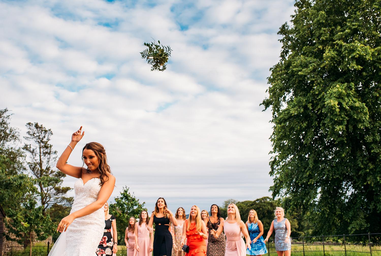 colour photo, bride throwing bouquet
