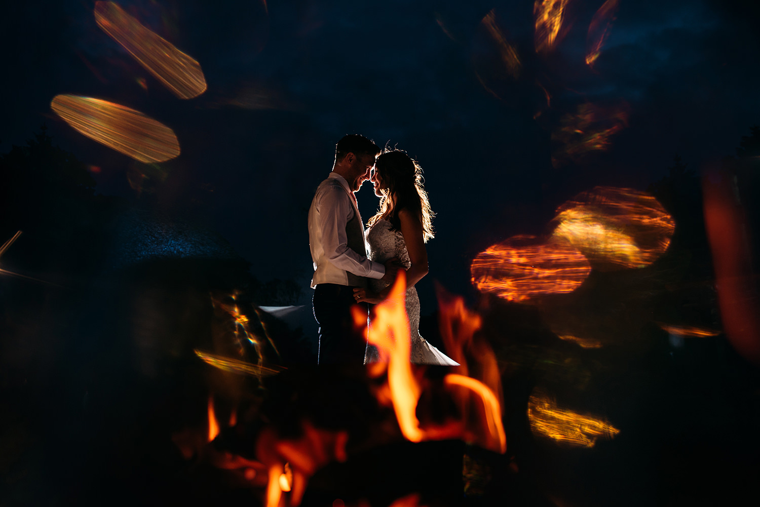 colour photo of bride and groom by a fire pit