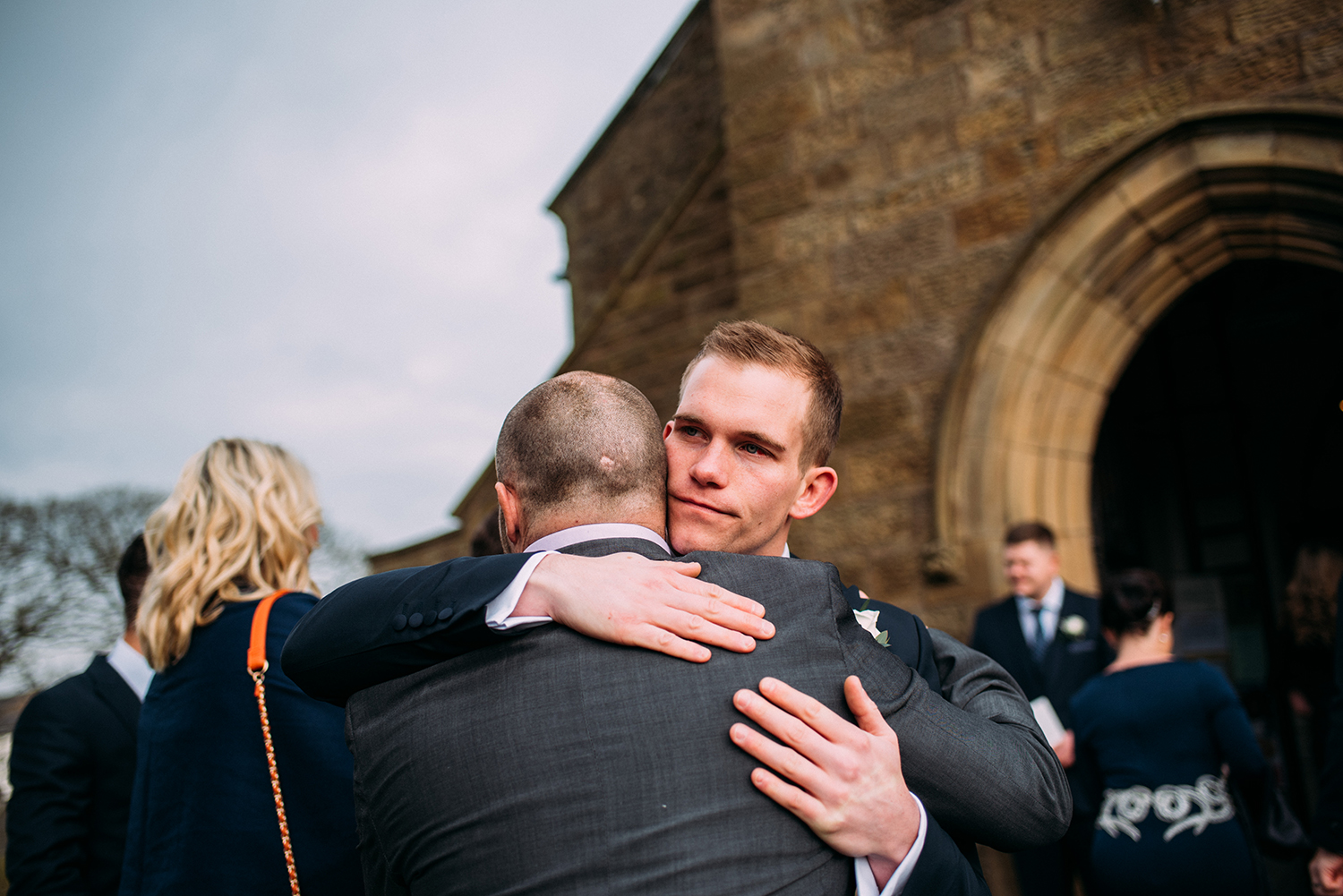 Groom hugging friend