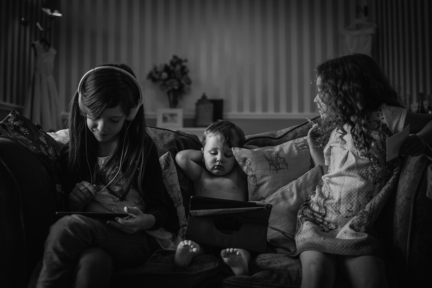Black and white photo of 3 kids watching ipads on a sofa