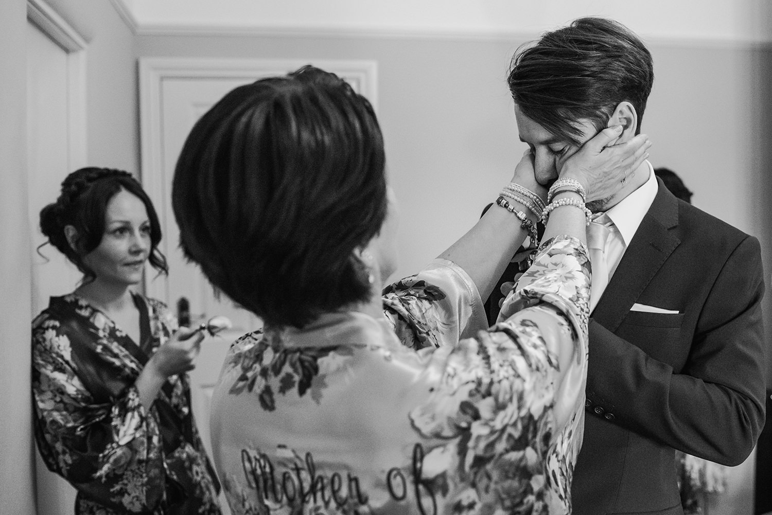 groom's mother squeezing his cheeks
