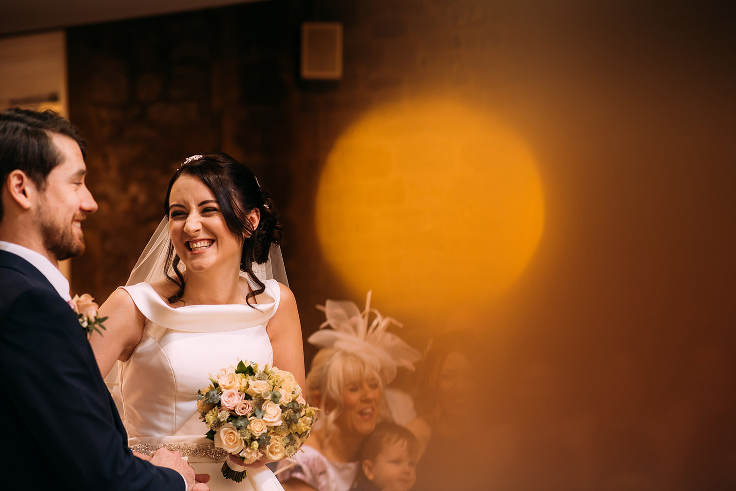 bride and groom in service, with orange bokeh