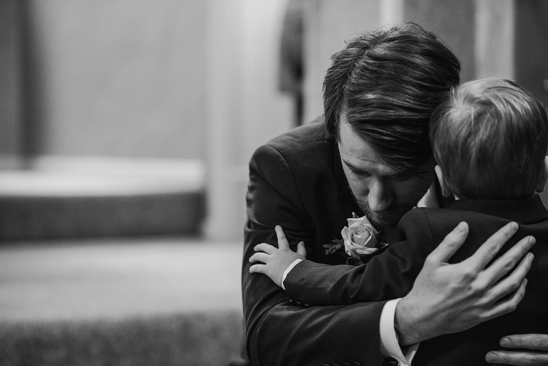 groom hugging his son