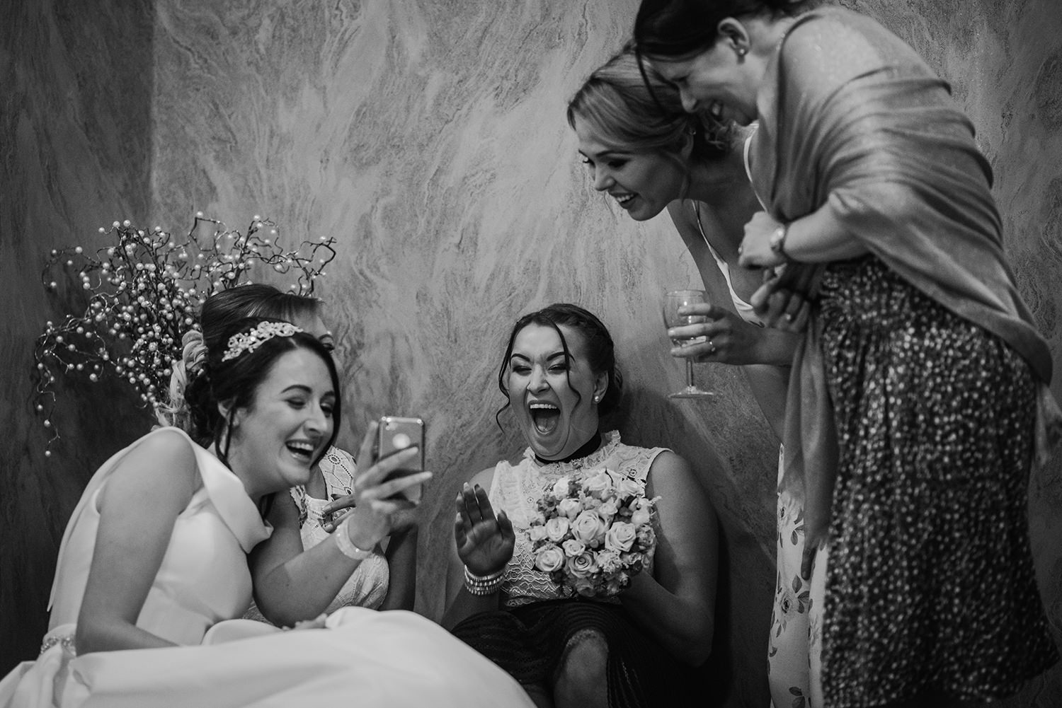 girls laughing at something on a phone screen