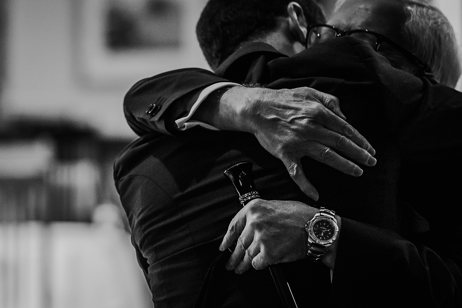 black and white image of groom hugging father of the bride